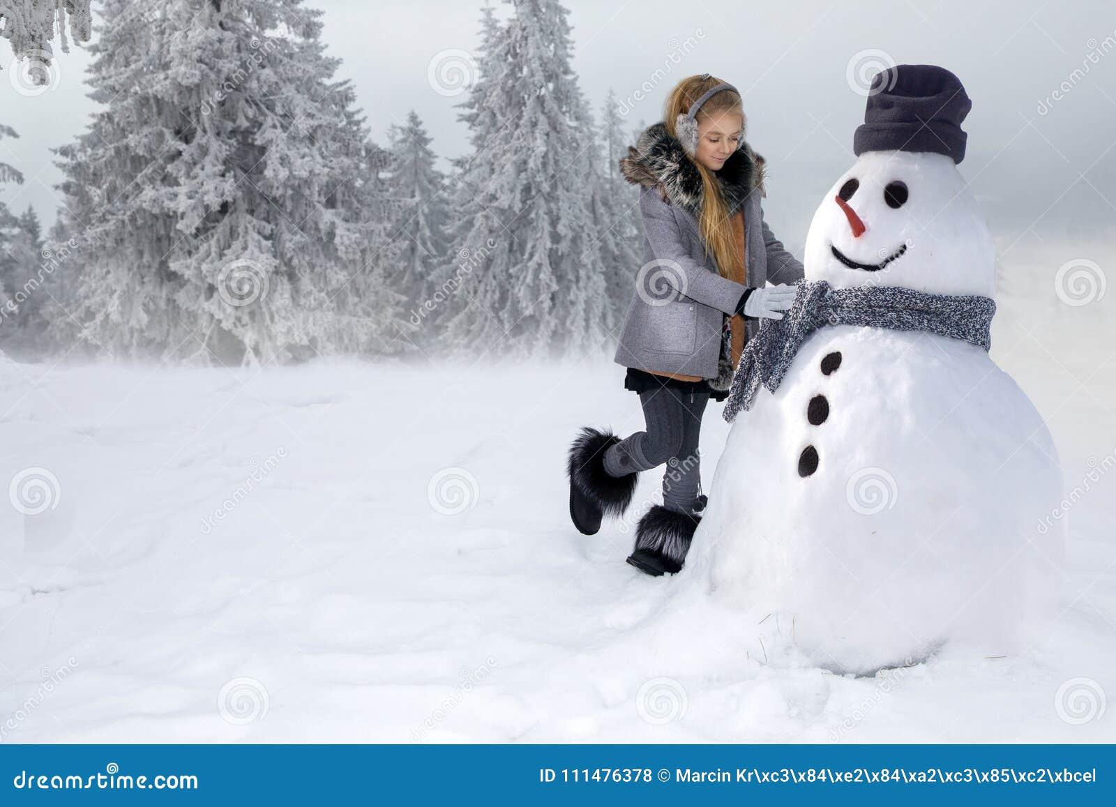 Śliczna mała dziewczynka, stojący na śniegu i robi bałwanu z śniegiem Dziewczyna ubiera w zimy odzieży