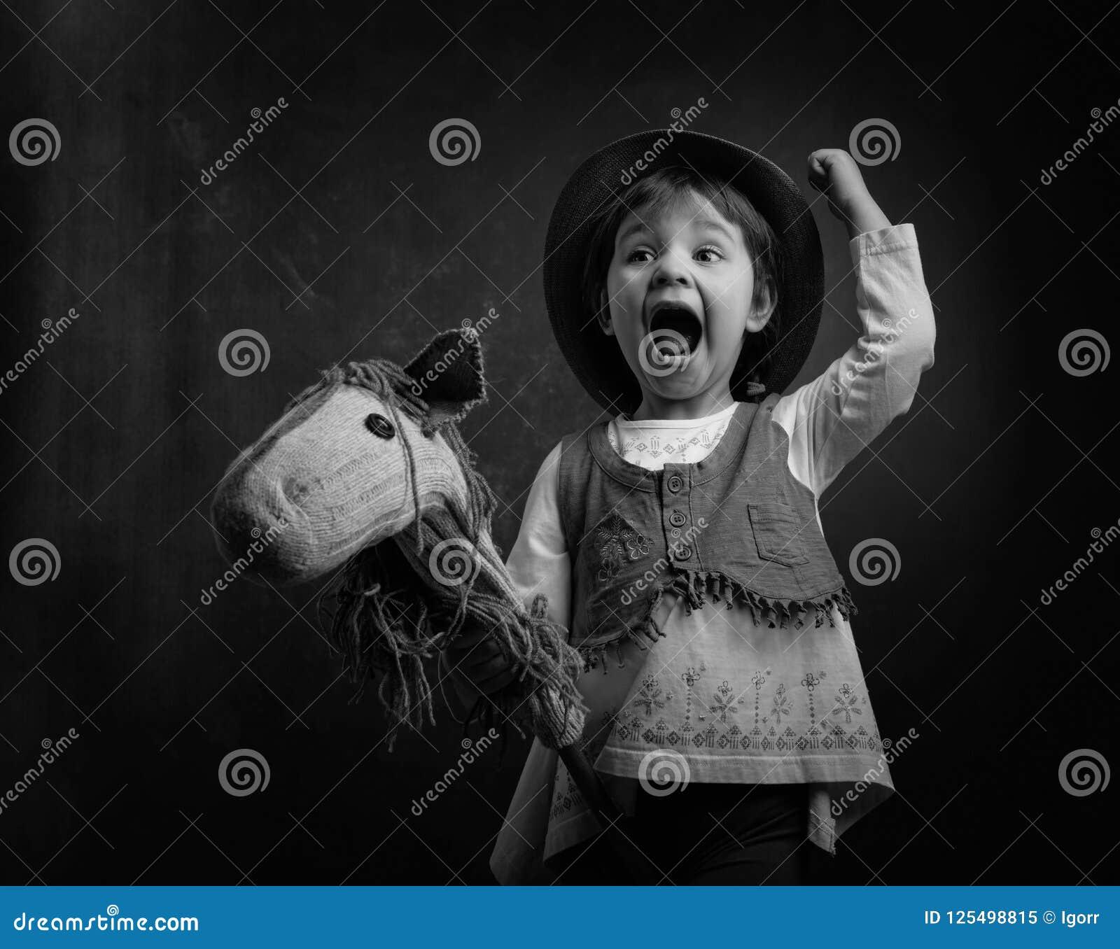 Śliczna mała dziewczynka ubierał jak kowboj bawić się z domowej roboty h