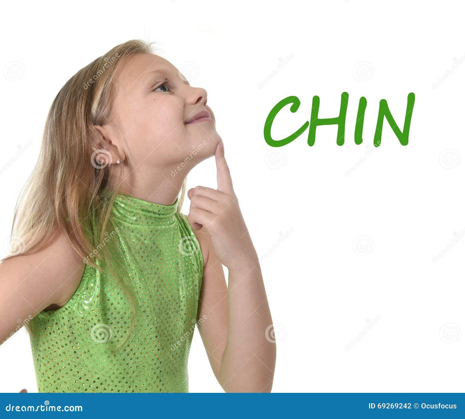 Śliczna mała dziewczynka wskazuje jej podbródek w częściach ciała uczy się angielszczyzn słowa przy szkołą