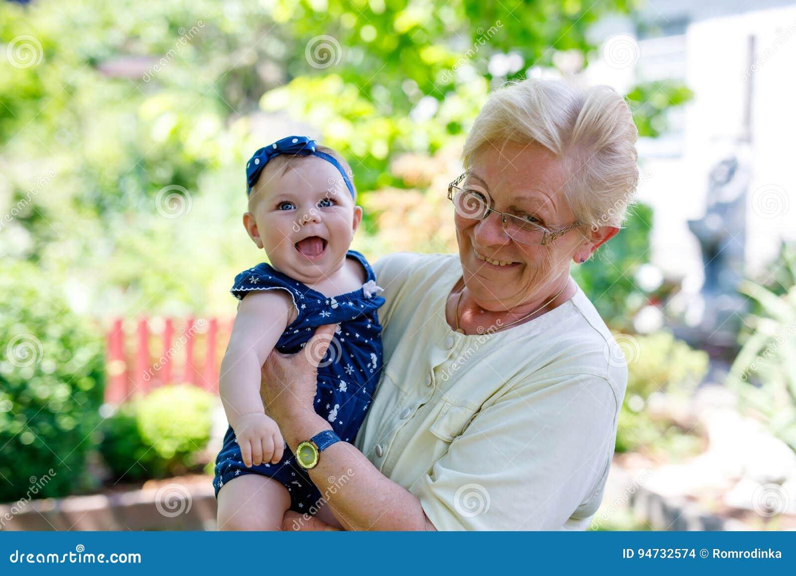 Śliczna mała dziewczynka z babcią na letnim dniu w ogródzie