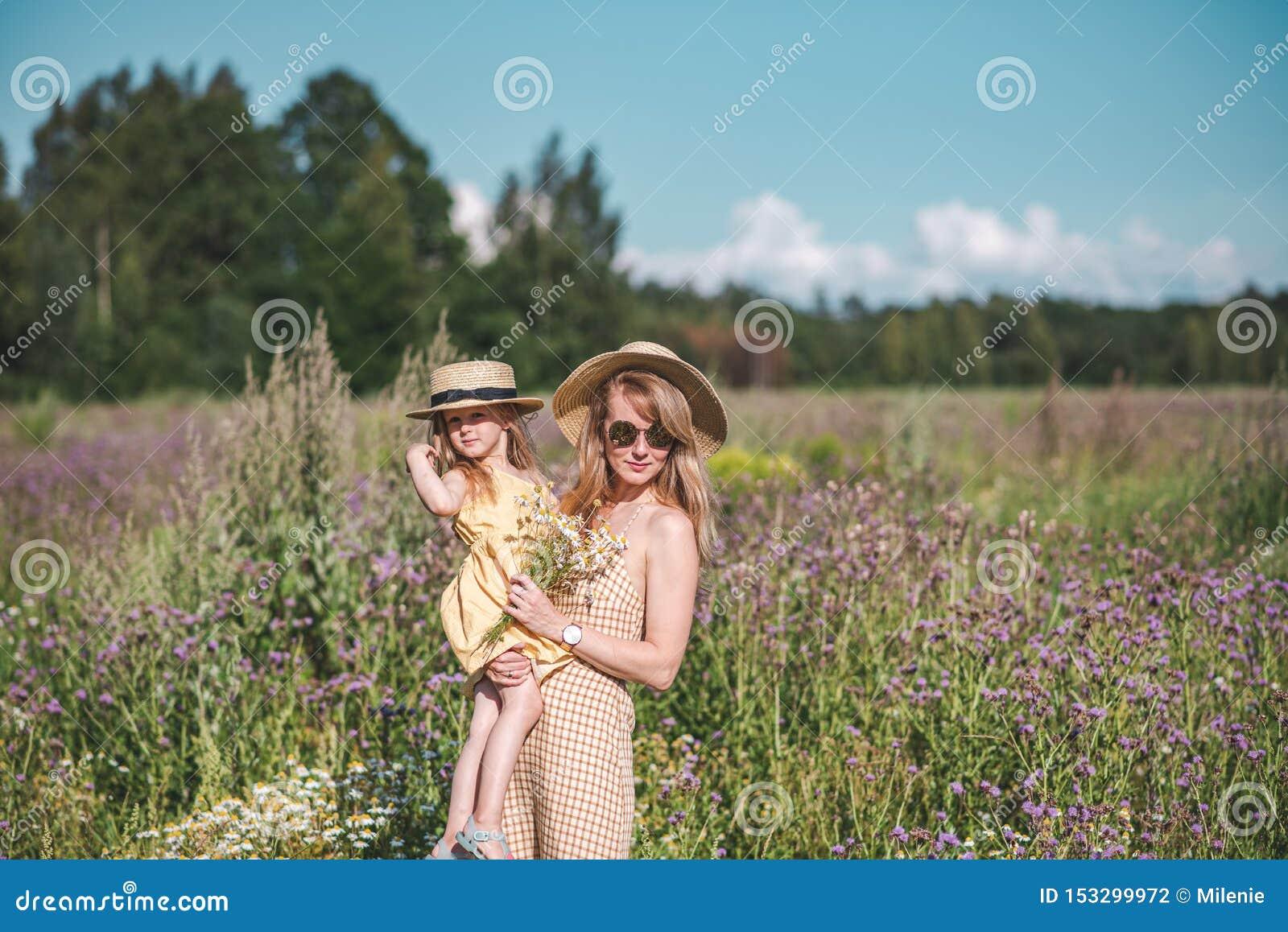 Śliczna mała dziewczynka z jej macierzystym odprowadzeniem w kwiatu polu