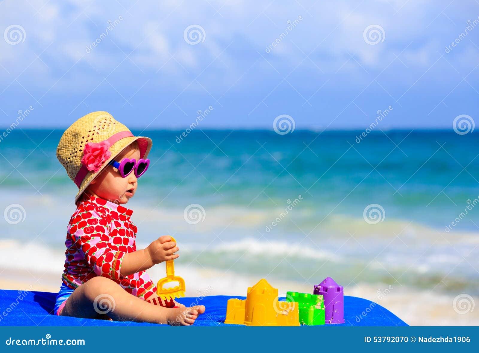 Śliczna mała dziewczynka z piaskiem bawi się na plaży
