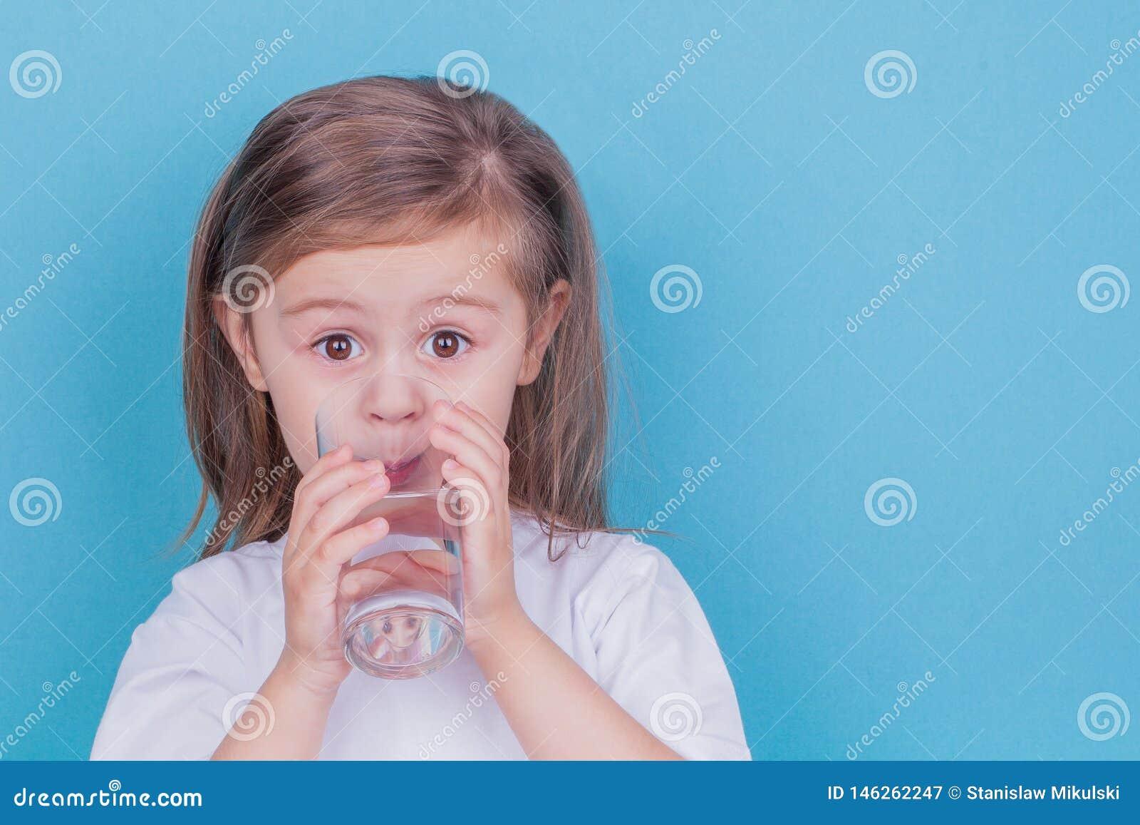 Śliczna małej dziewczynki woda pitna od szkła