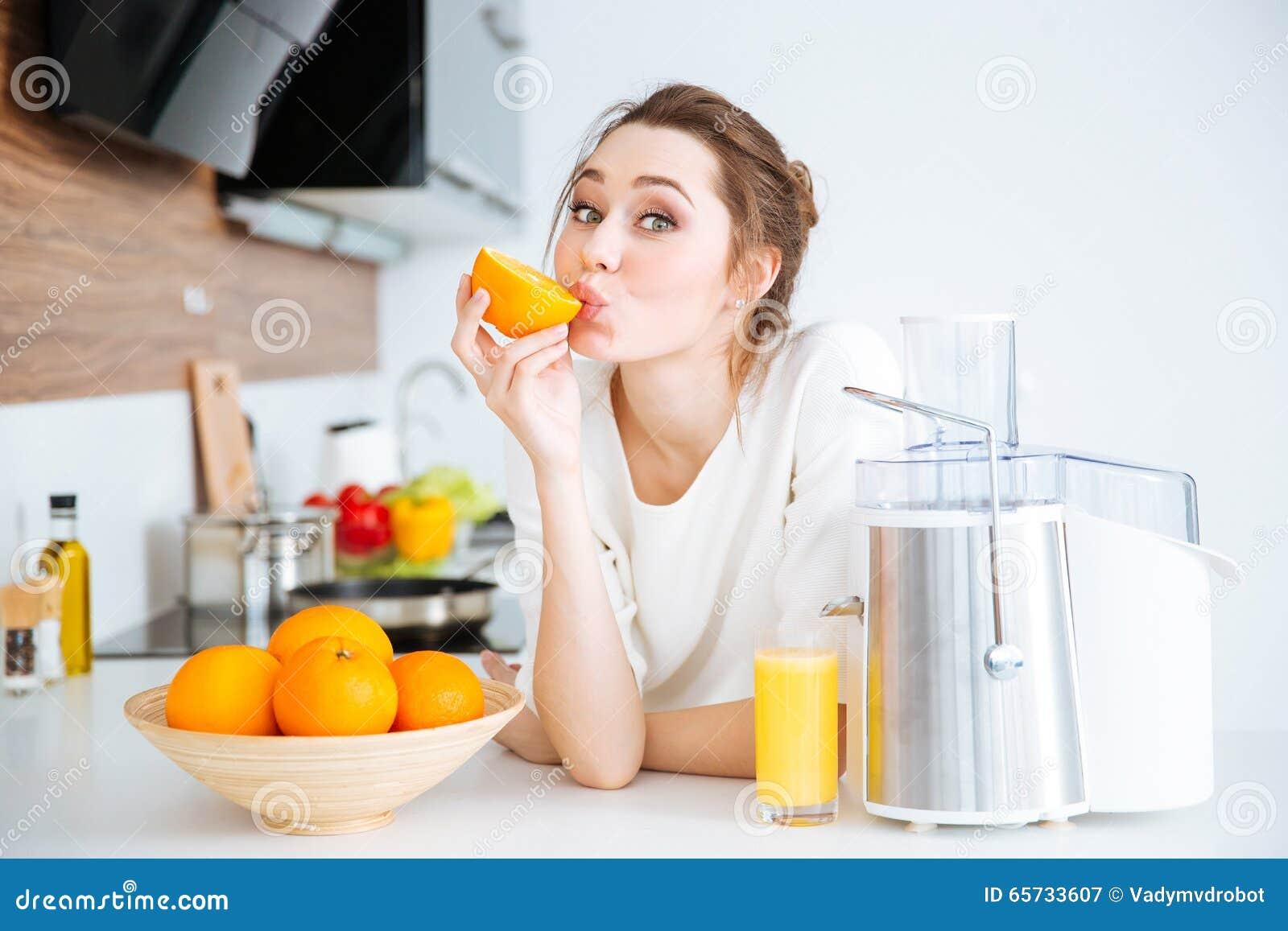 Śliczna powabna kobieta robi sokowi i je pomarańcze