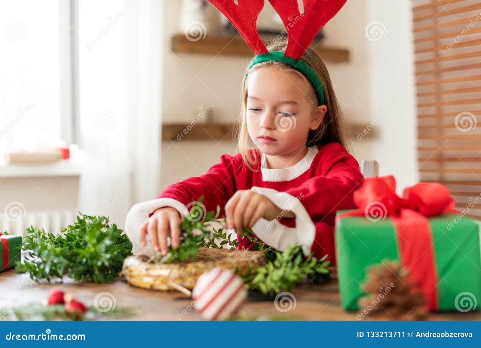 Śliczna preschooler dziewczyna jest ubranym reniferowych poroże robi boże narodzenie wiankowi w żywym pokoju ubierał w reniferowy