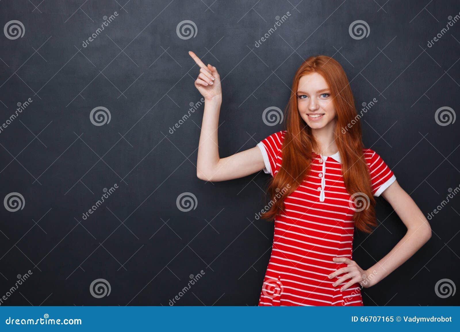 Śliczna szczęśliwa kobieta wskazuje na copyspace nad chalkboard tłem