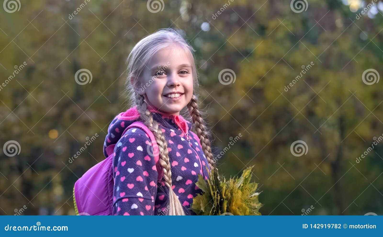 Śliczna szkolna dziewczyna z bukietem spadać liście pozuje dla kamery, jesieni przespacerowanie