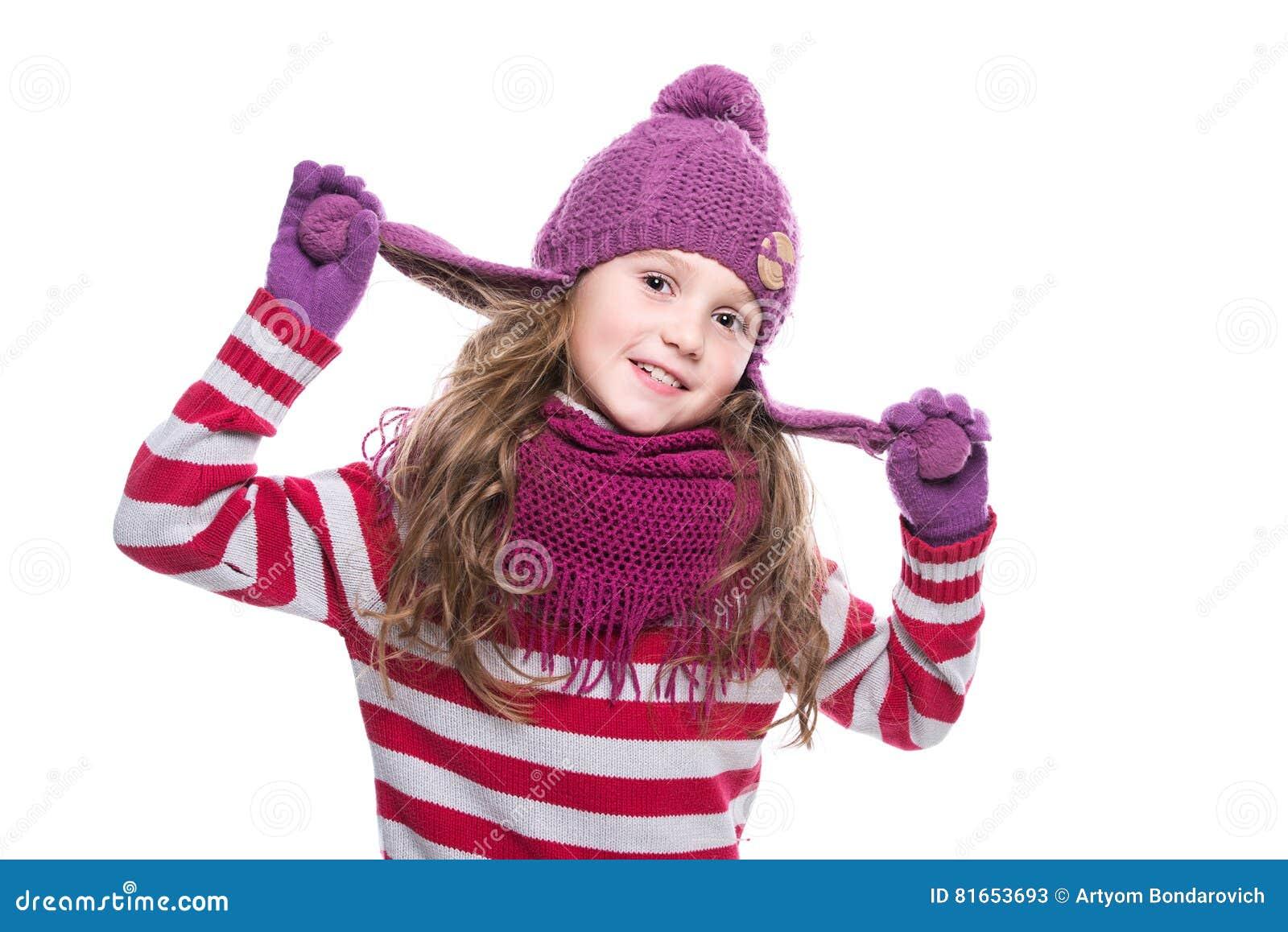 Śliczna uśmiechnięta mała dziewczynka jest ubranym purpury dział szalika, kapelusz i rękawiczki na białym tle, Zima odziewa