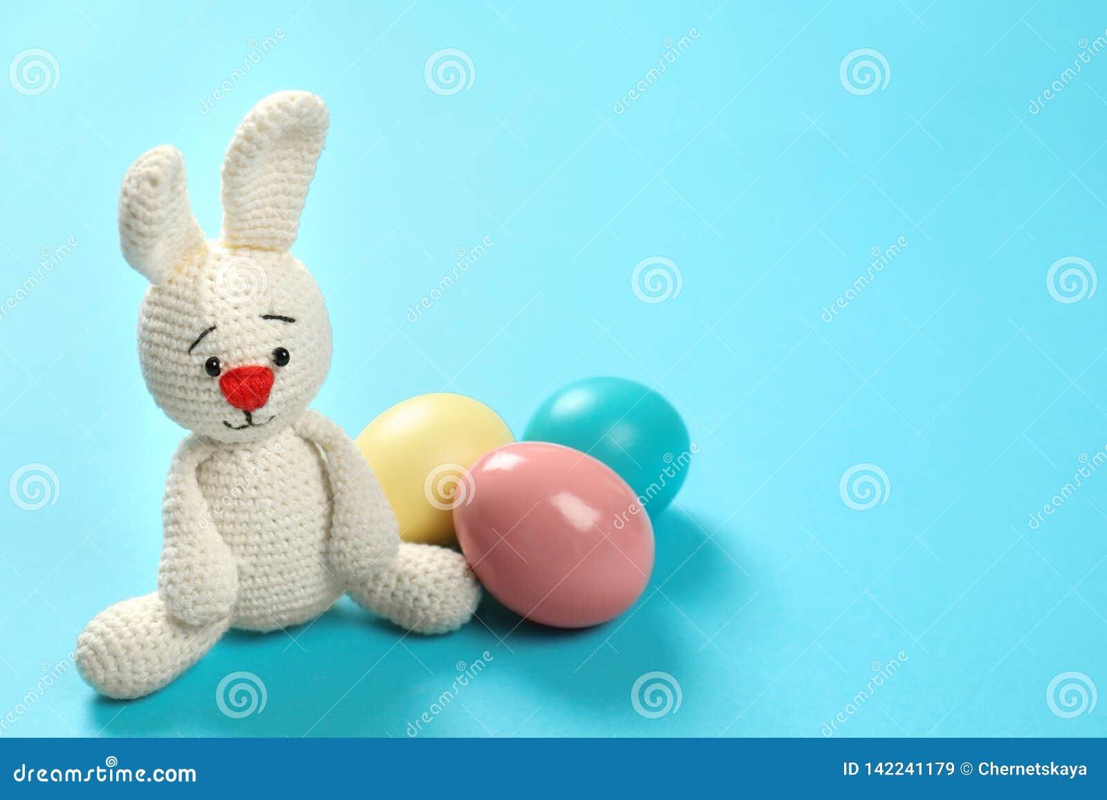 Śliczna Wielkanocnego królika zabawka i farbujący jajka na koloru tle