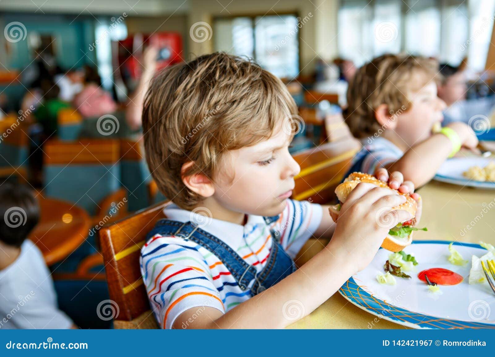 Śliczna zdrowa preschool dzieciaka chłopiec je hamburgeru obsiadanie w szkoły lub pepiniery kawiarni Szczęśliwy dziecko je zdrowy