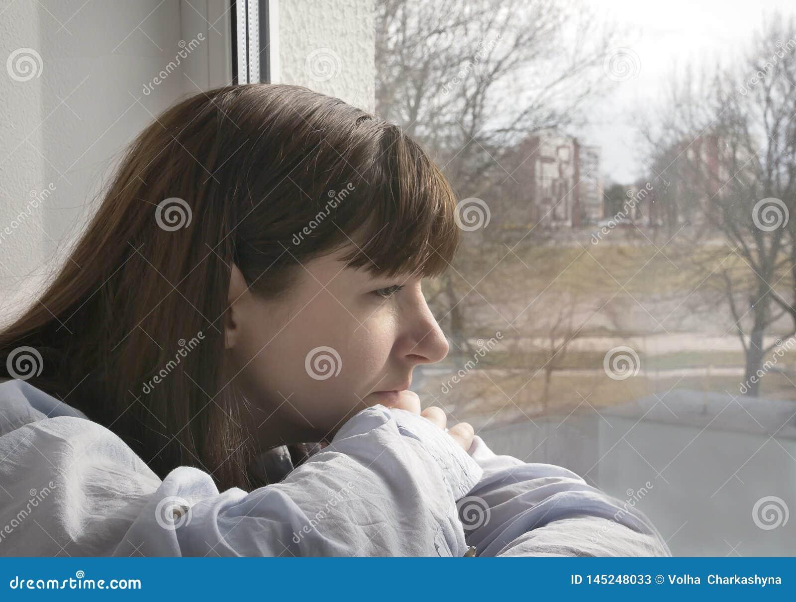 Ślicznej młodej brunetki kobiety smutny przyglądający okno, w górę