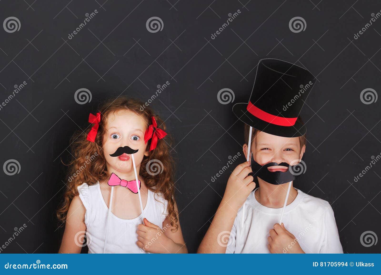 Śliczni bliźniaków dzieciaki trzymają karnawałowego wąsy i brodę, ojca dnia przeciw