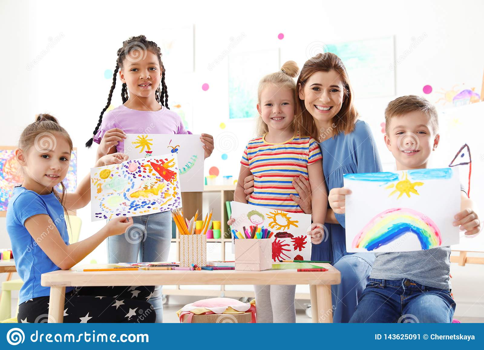 Śliczni małe dzieci z nauczycielem pokazuje ich obrazy przy lekcją