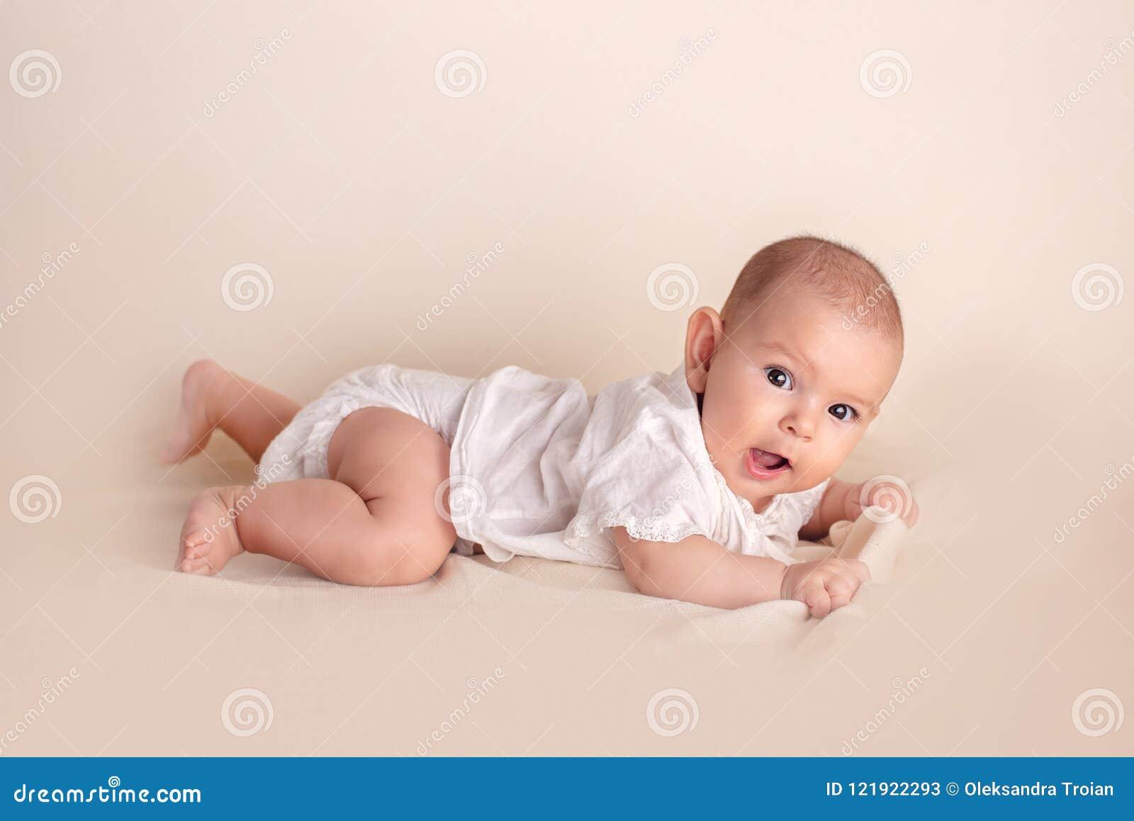 Śliczny śmieszny dziecko kłama na białej koc z dużymi pięknymi oczami