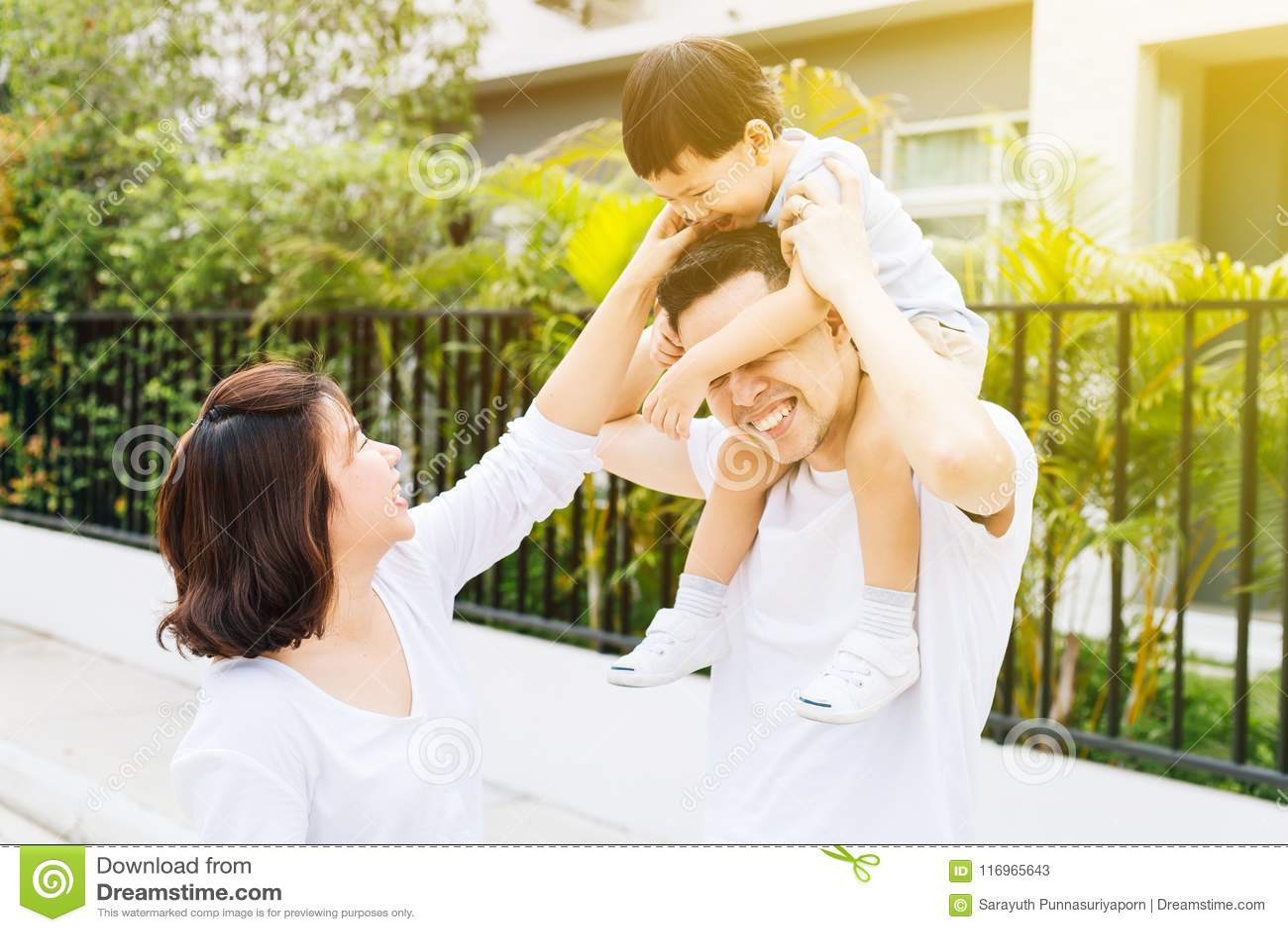 Śliczny Azjatycki ojciec piggbacking jego syna wraz z jego żoną w parku Z podnieceniem rodzinny wydaje czas wraz z szczęściem