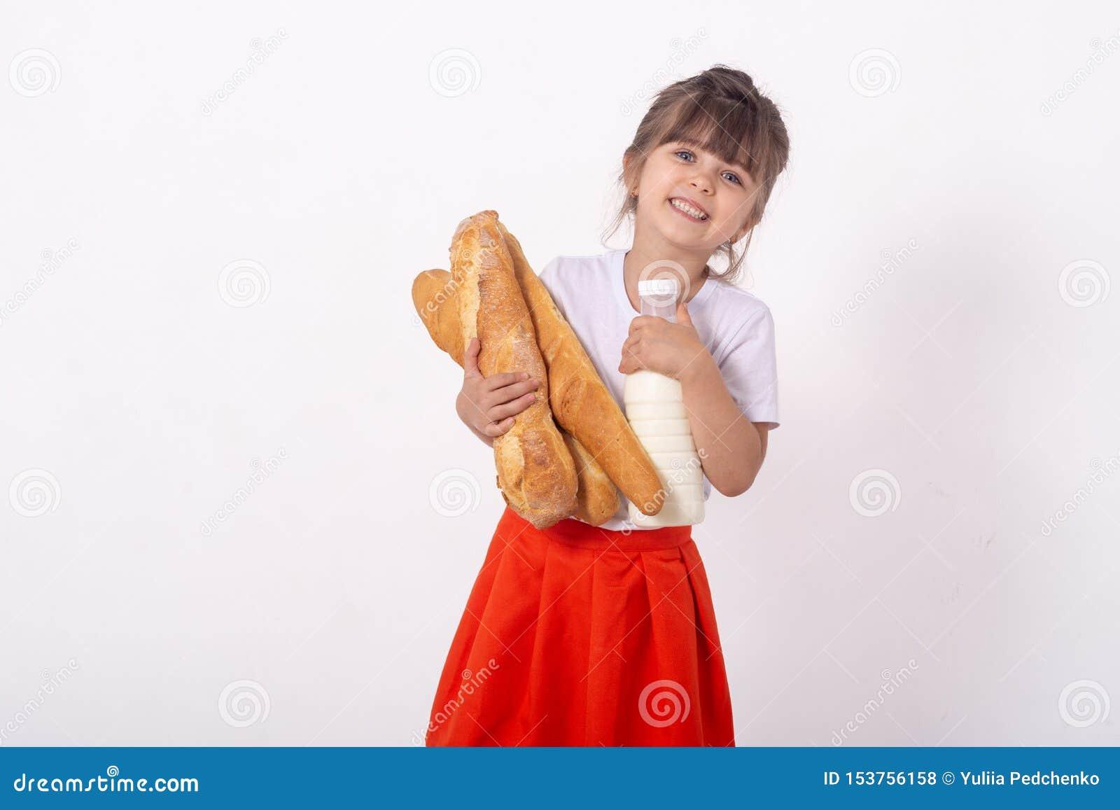Śliczny dzieciak z Francuskim chlebem w rękach Świeżo piec mleko na białym tle i chleb, Jedzenie dla młodej rodziny z ki