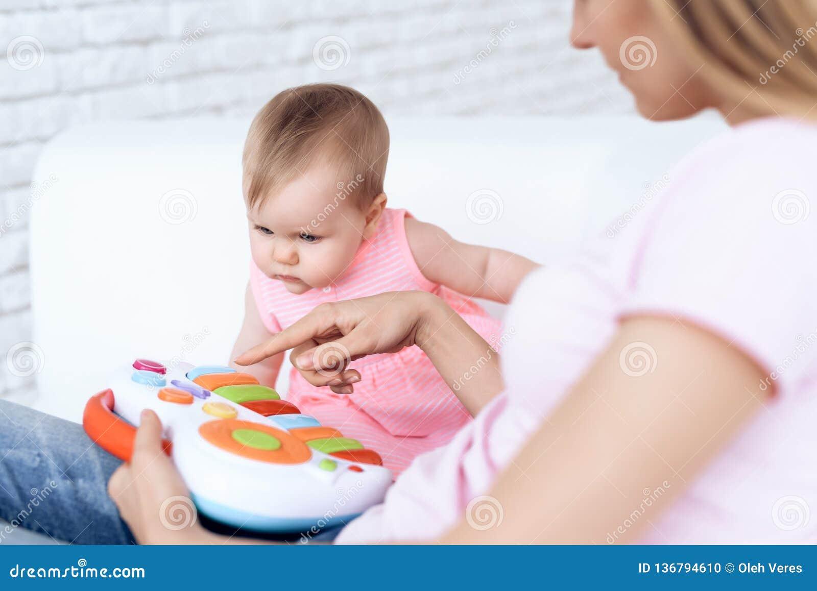 Śliczny dziecko bawić się zabawkę na kanapie z matką
