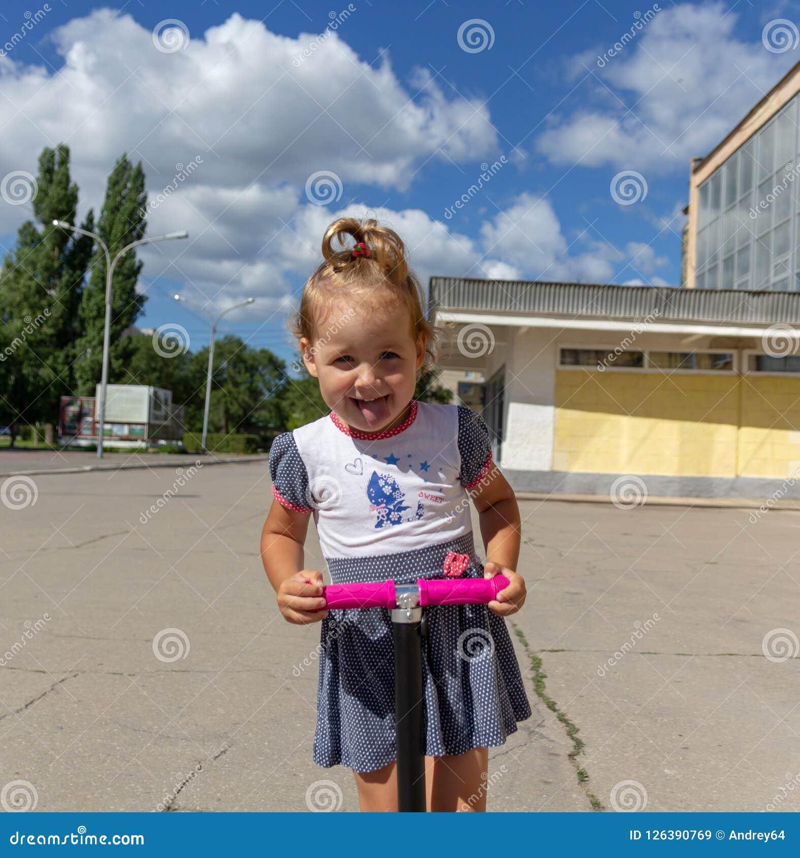 Śliczny dziecko zręcznie jeździć na łyżwach na różowej dwukołowej hulajnoga na s