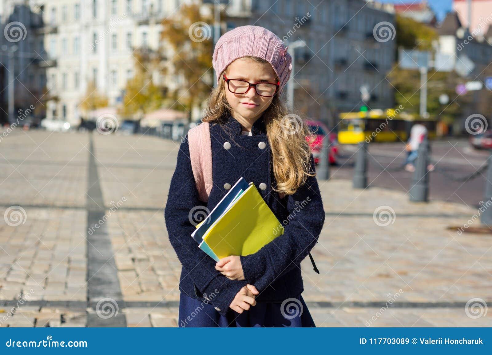 Śliczny dziewczyny dziecko z plecakiem, notatniki, w francuza berecie i żakiecie tło miejskie