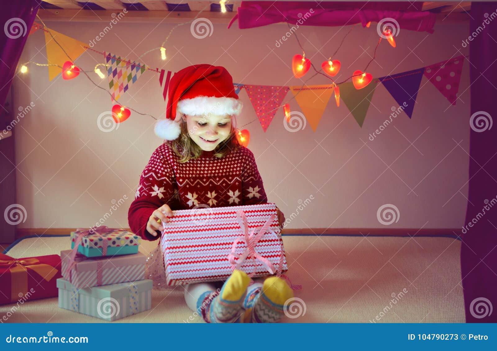 Śliczny dziewczyny otwarcia pudełko z Bożenarodzeniową teraźniejszością