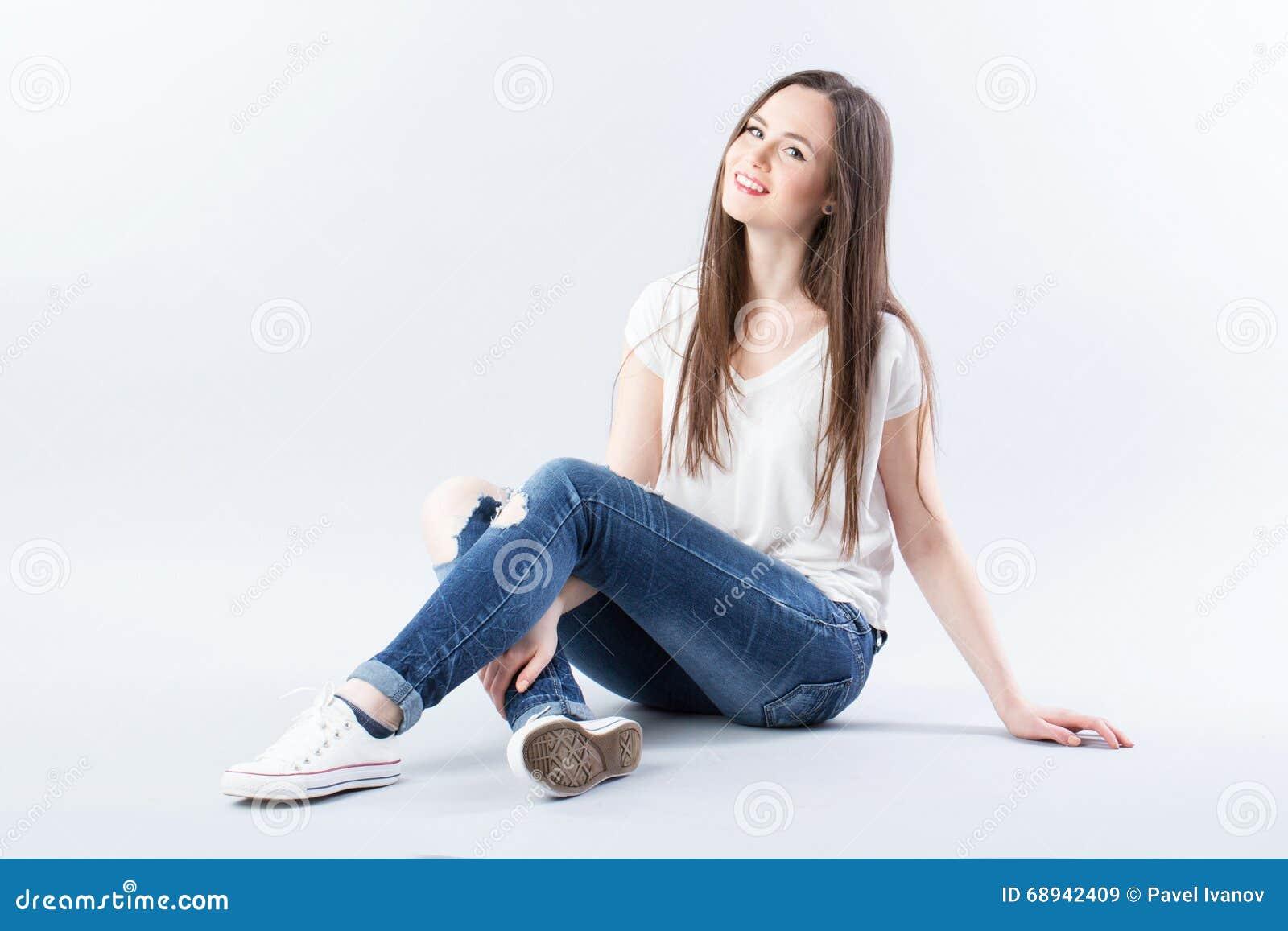 Śliczny kobiety obsiadanie na ono uśmiecha się i podłoga