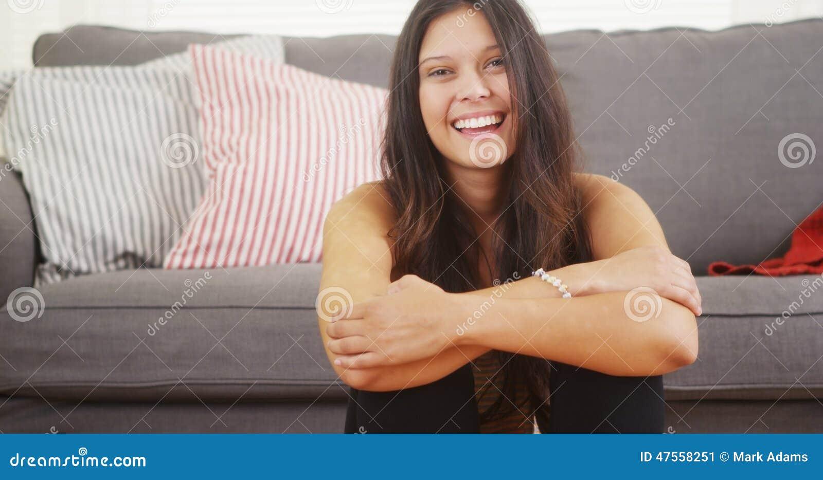 Śliczny kobiety obsiadanie w żywy izbowy roześmianym uśmiechnięty i