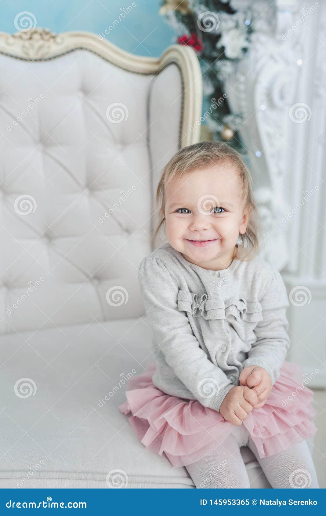 śliczny małego dziecka obsiadanie w krześle blisko choinki szcz??liwego nowego roku, ma?y portret dziewczyny Bo?enarodzeniowy poj
