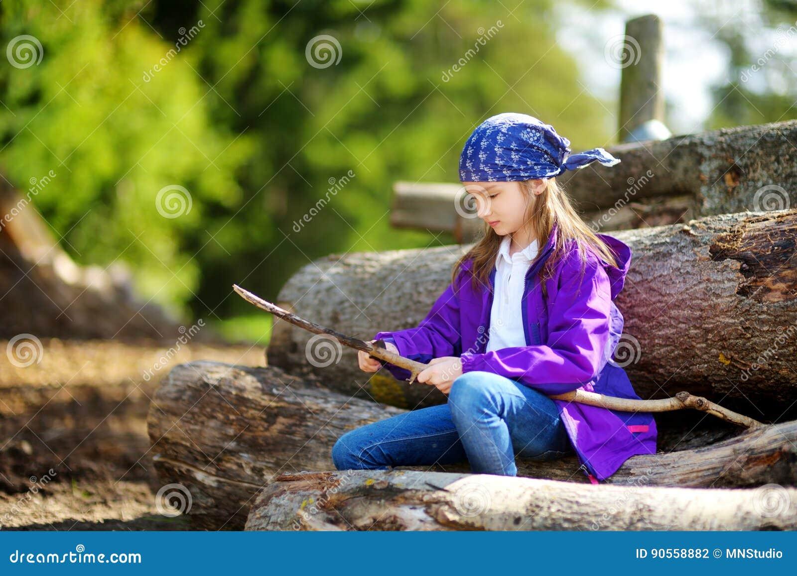Śliczny małej dziewczynki obsiadanie na drzewnych belach używać kieszeniowego nóż strugać wycieczkuje kij