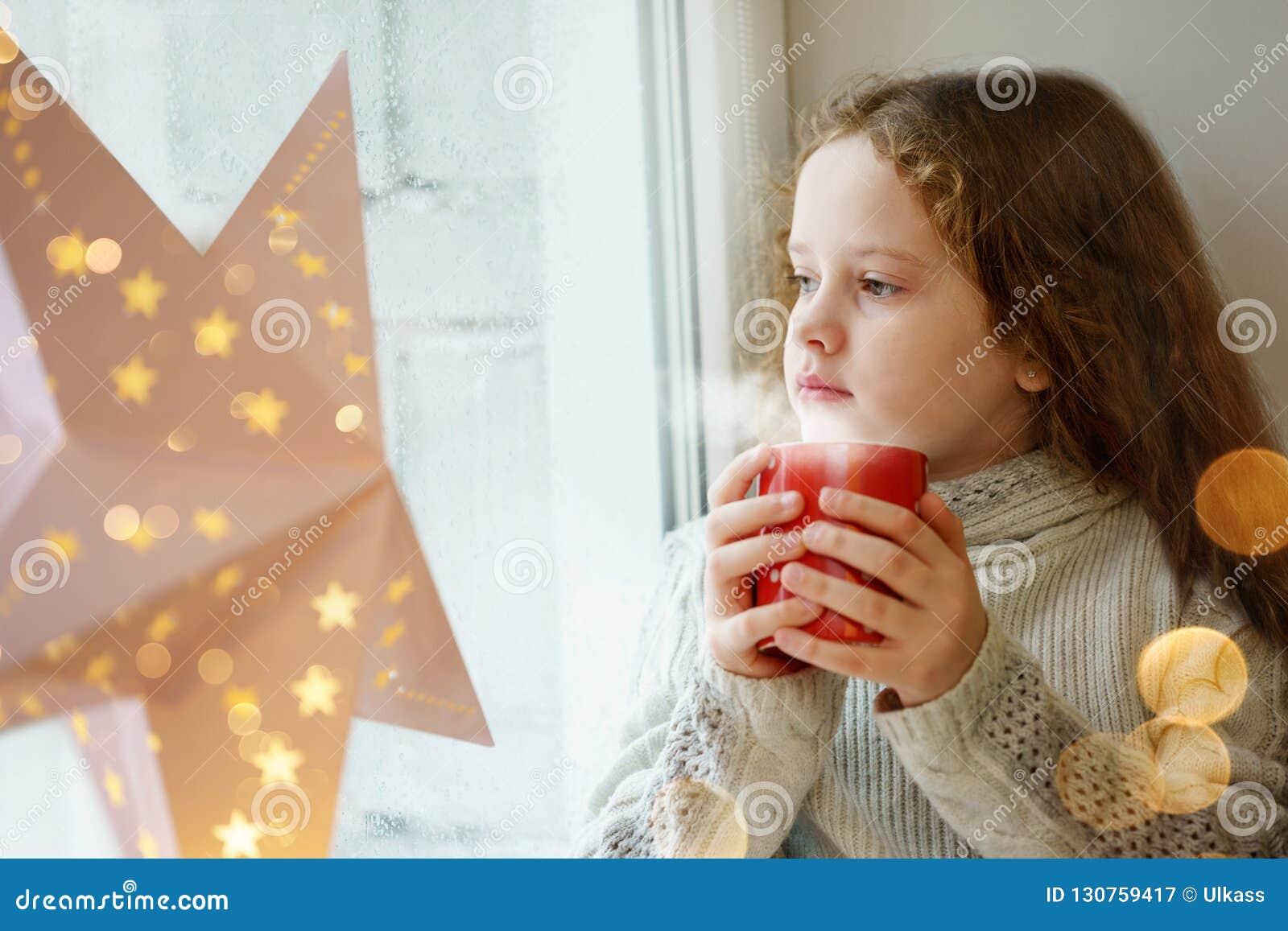 Śliczny małej dziewczynki obsiadanie z filiżanką gorący kakao okno a