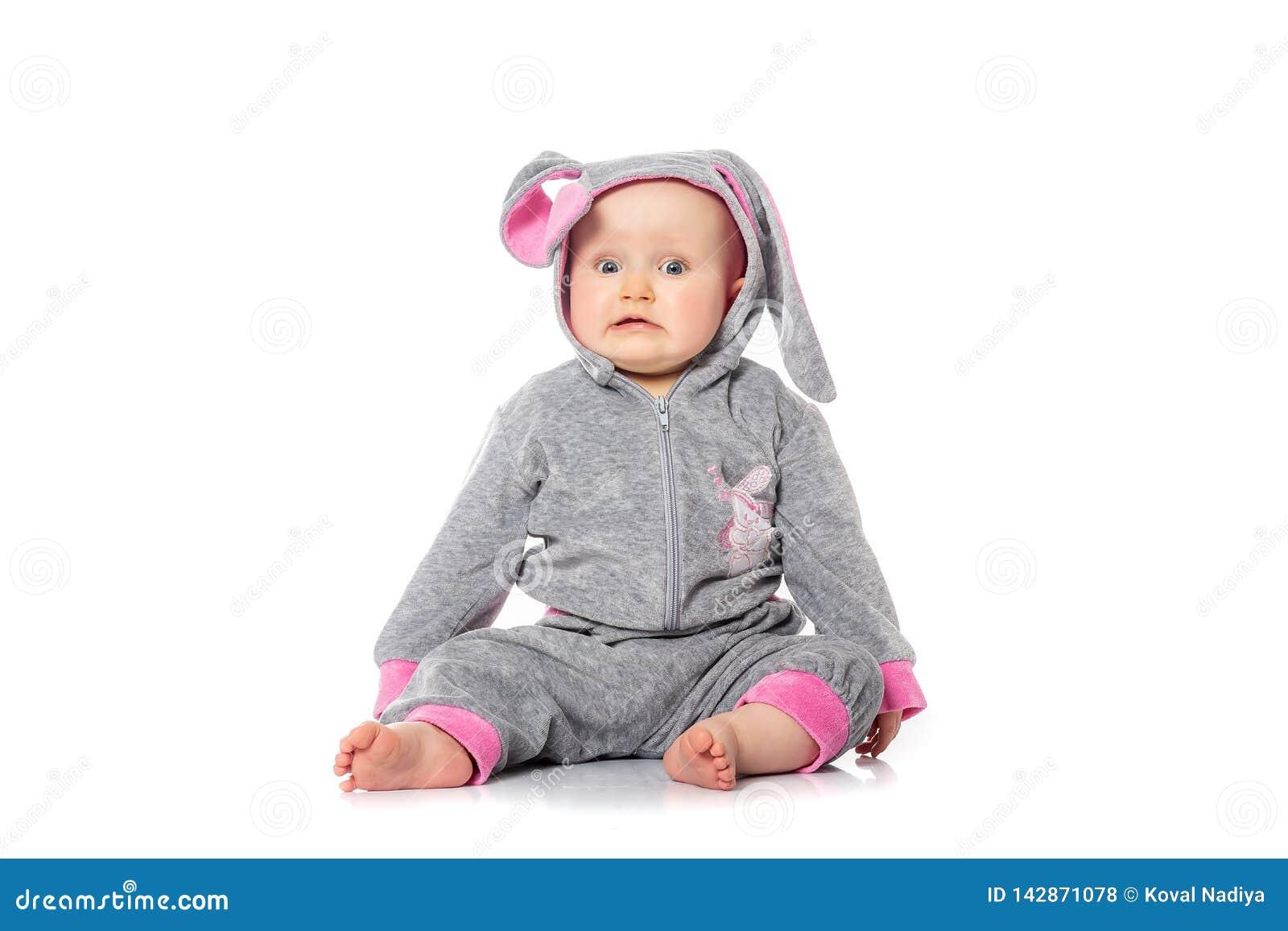 Śliczny mały dziecko w królika kostiumowym obsiadaniu na białym tle śniadanie na Wielkanocnym ranku Dzieciaki świętuje wielkanoc