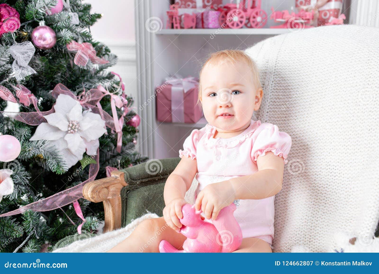 Śliczny mały dziecko w rocznika krześle i boże narodzenie prezentach Małe dziecko ma zabawę blisko choinki w żywym pokoju