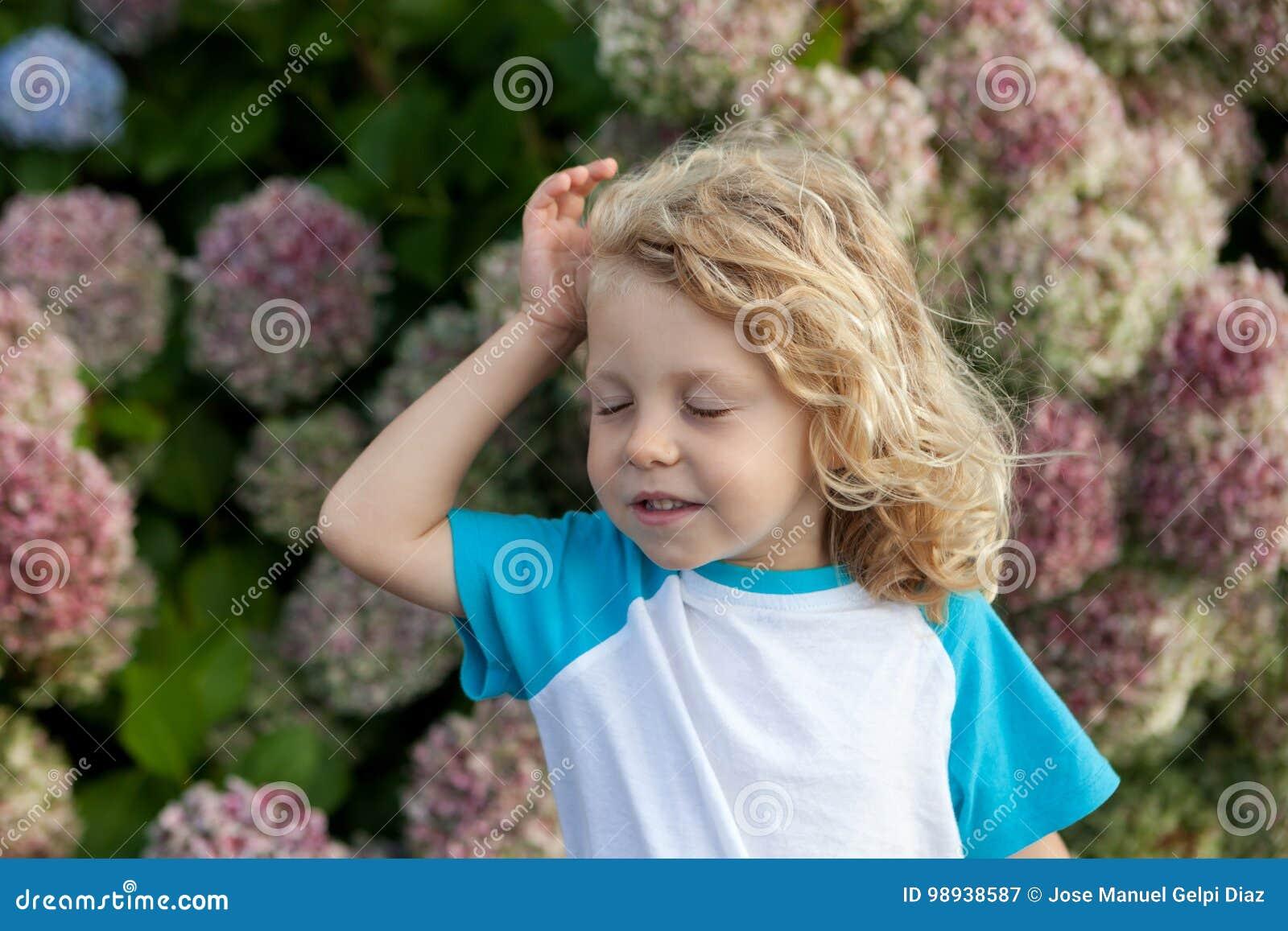 Śliczny mały dziecko z dużo kwitnie w ogródzie