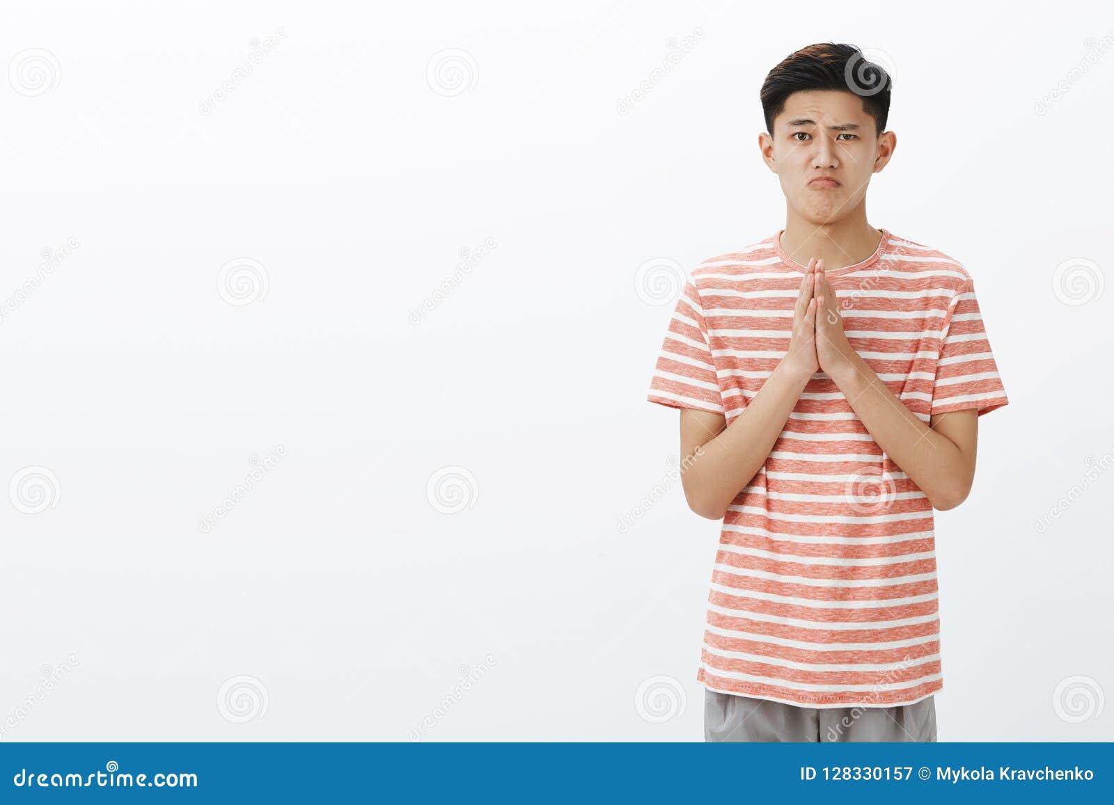 Śliczny niemądry facet szczerze pyta przebaczenie lub pozwolenie trzyma ręki, wewnątrz ono modli się nad klatką piersiową robi śl
