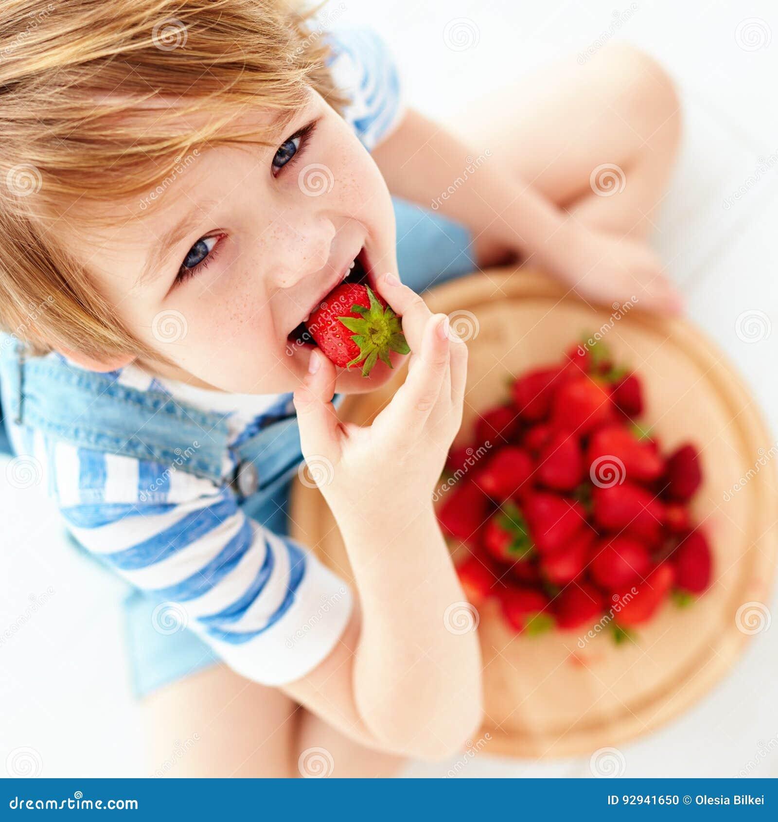 Śliczny szczęśliwy dzieciak je smakowite dojrzałe truskawki