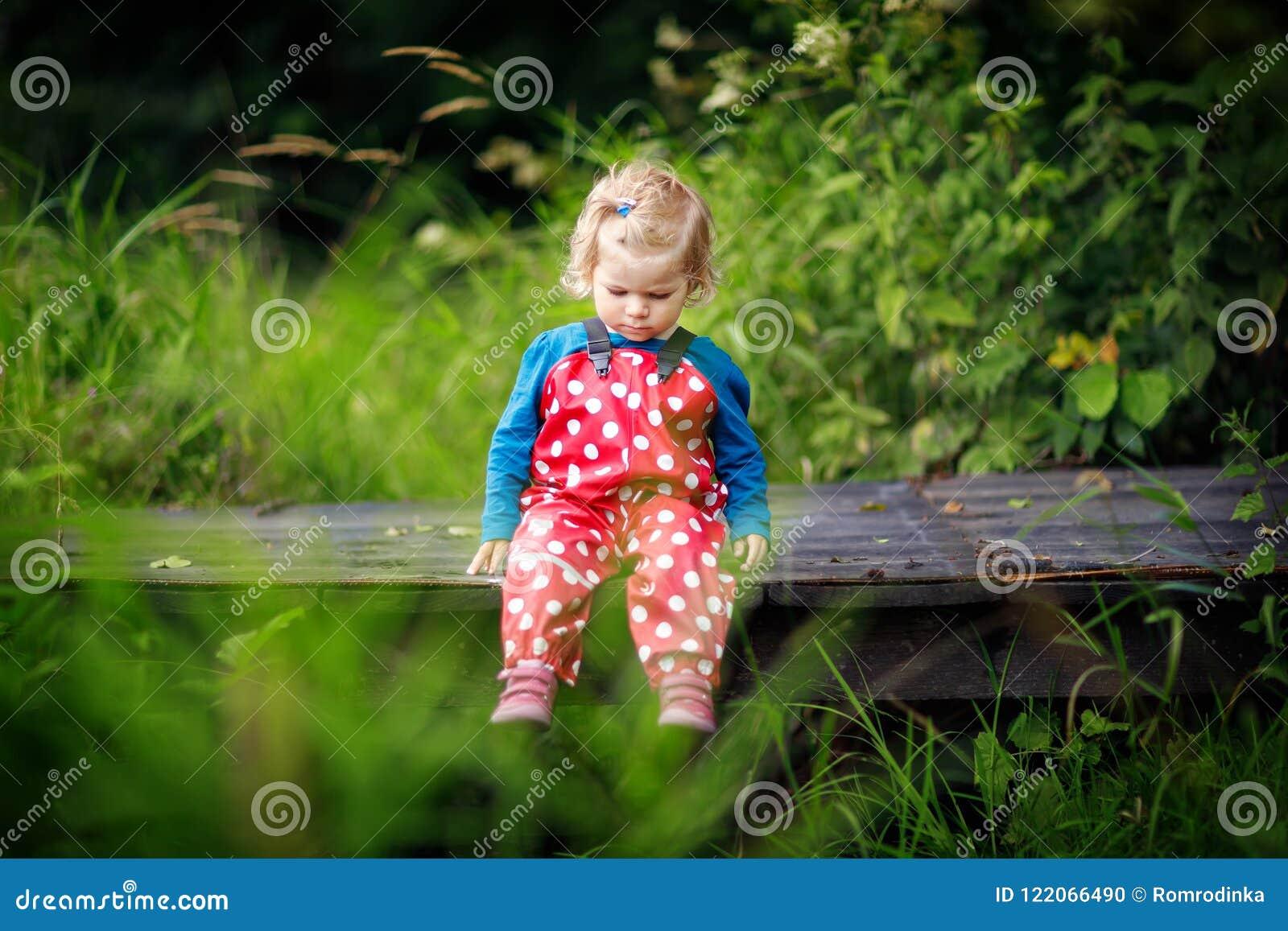 Śliczny uroczy berbeć dziewczyny obsiadanie na drewnianym moscie i miotanie małych kamieniach w zatoczkę Śmieszny dziecko ma zaba