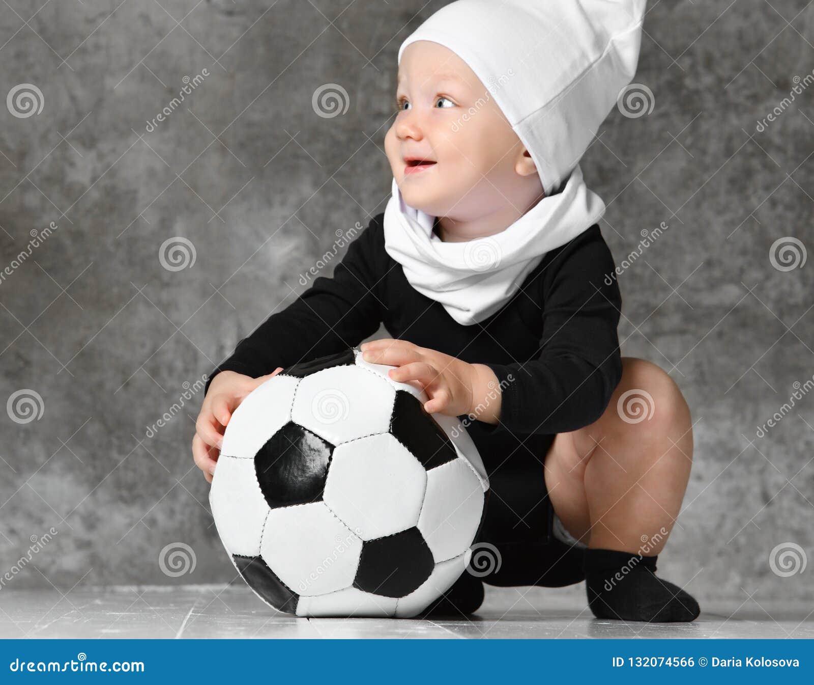 Śliczny wizerunek trzyma piłki nożnej piłkę dziecko