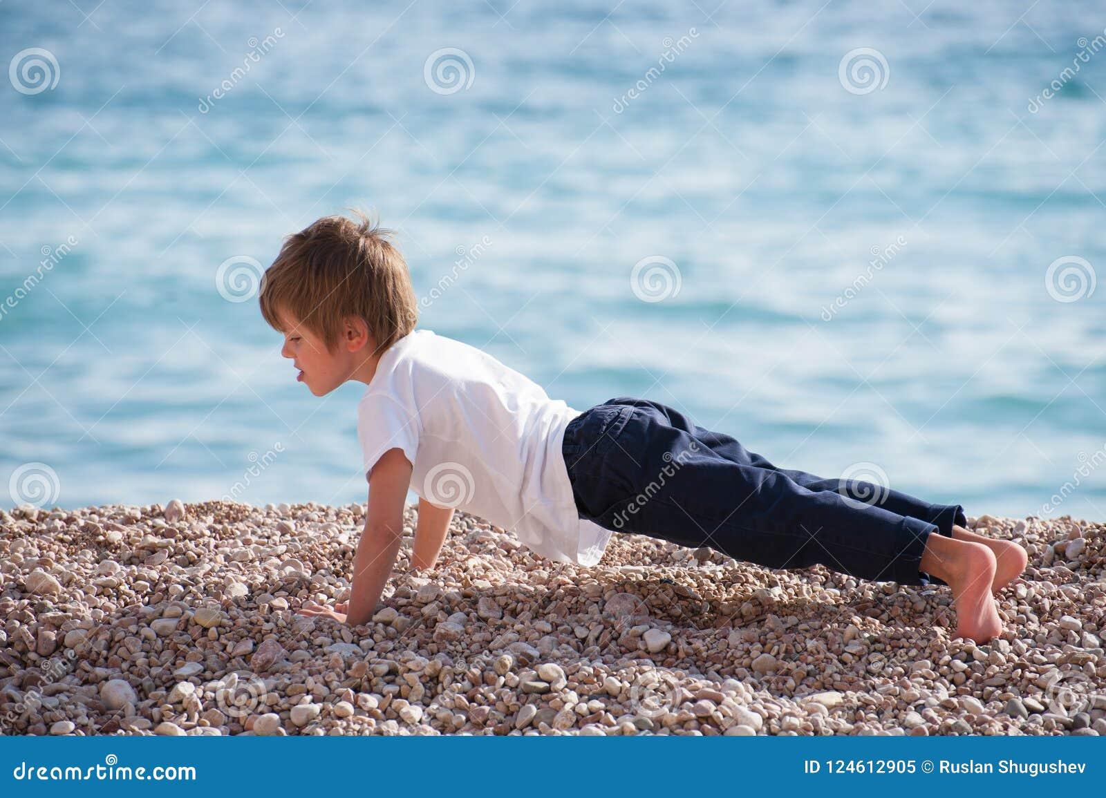 Śliczny zdrowy silny dzieciak robi pushups z wysiłkiem na dennym wybrzeżu w jesieni