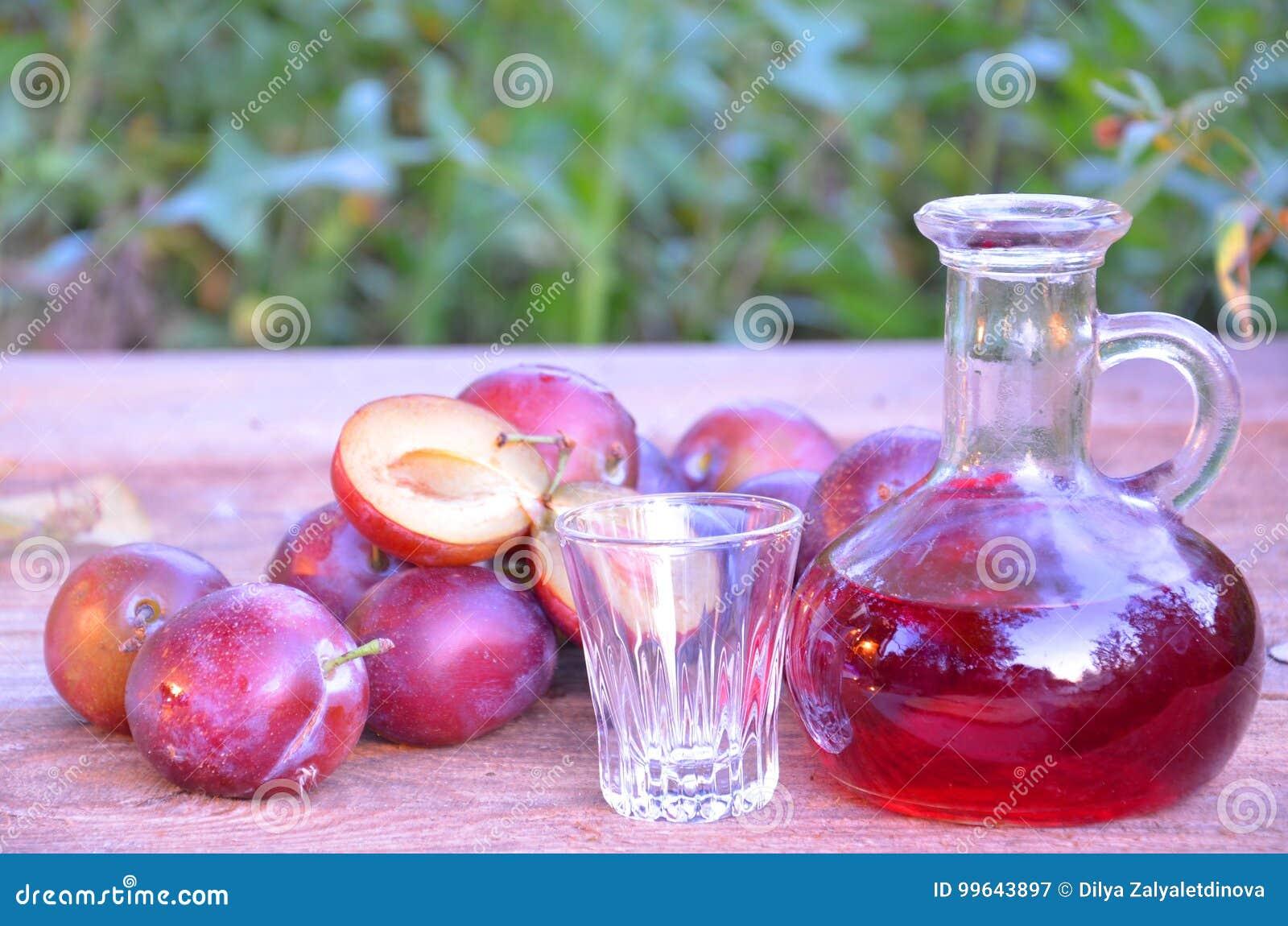 Śliwkowy brandy lub schnapps z śliwkami w trawie świeżymi i dojrzałymi Butelka domowej roboty brandy i osadzarki