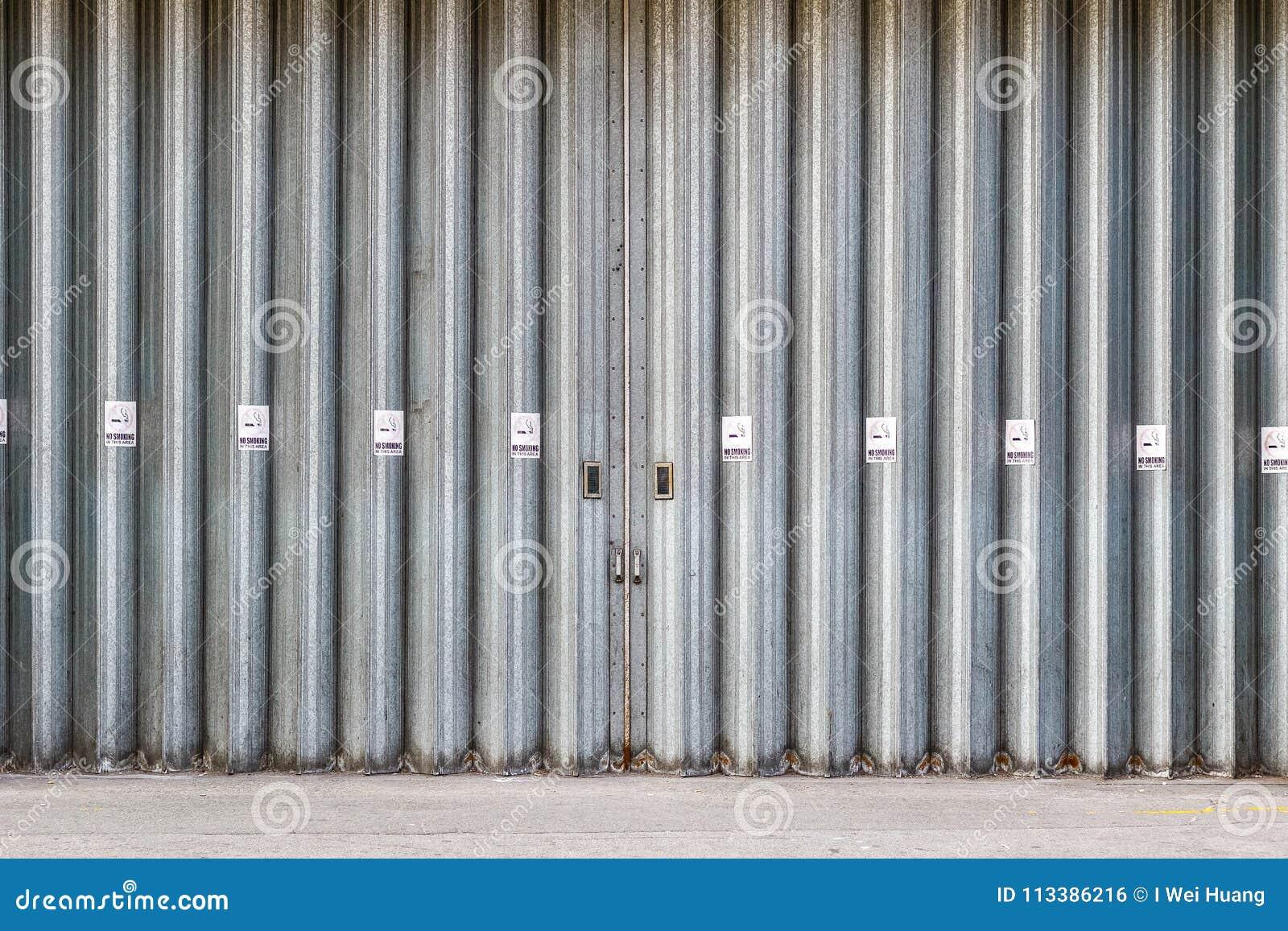 Ślizgający się przemysłowych drzwi z Palenie Zabronione znakami i składający