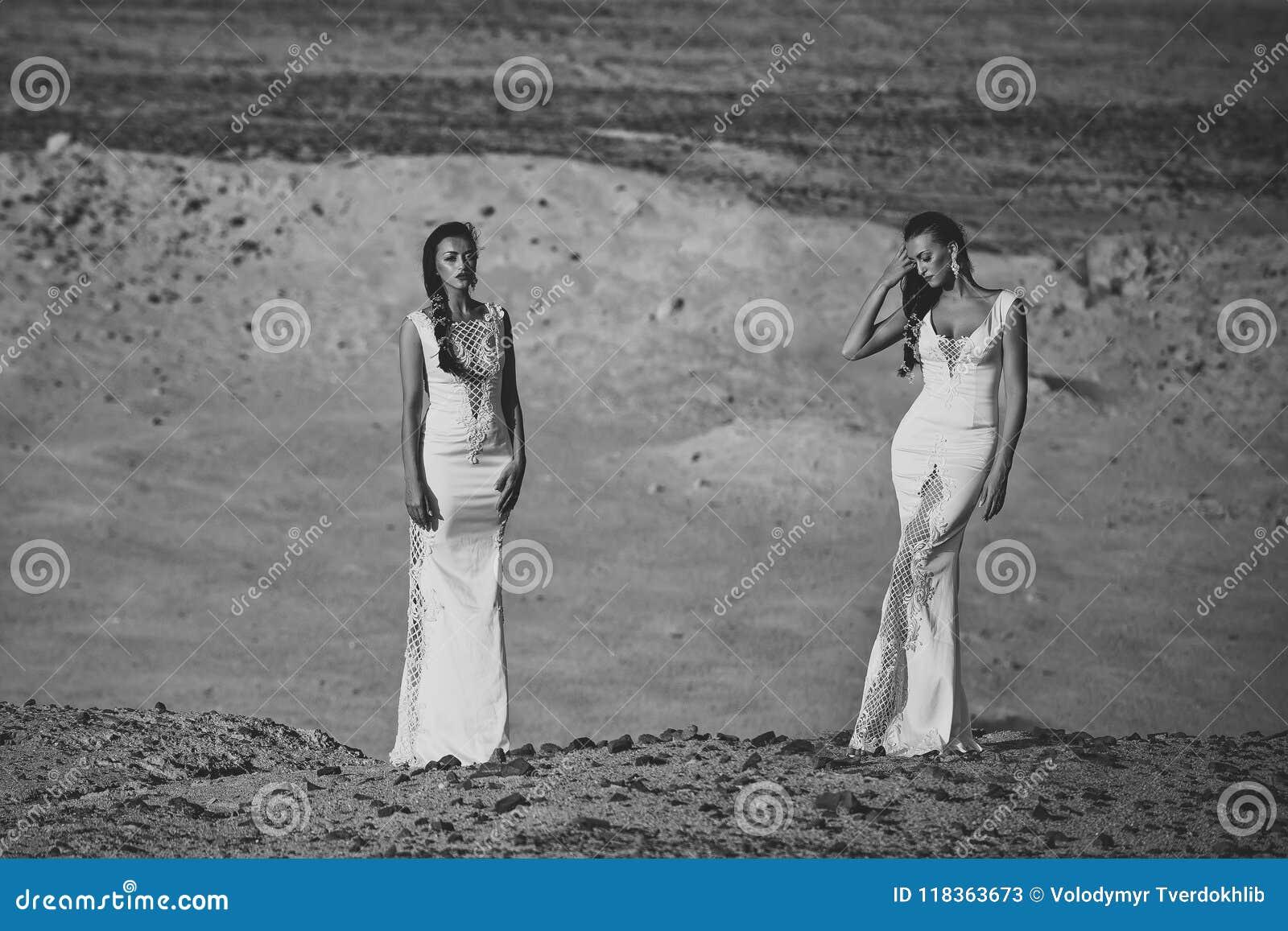 Ślubna agencja Dwa dziewczyny w białych sukniach pozuje w piasek diunach