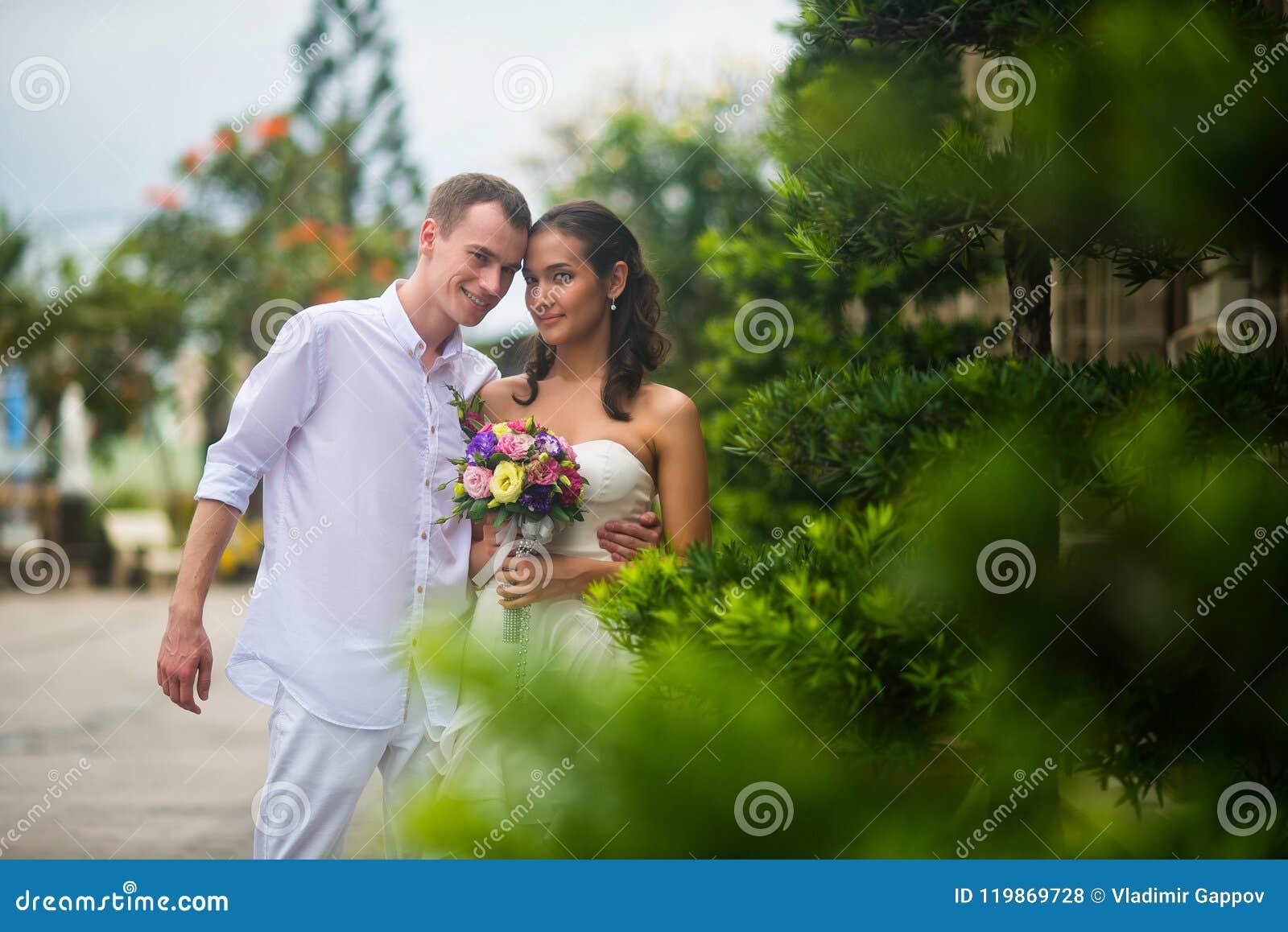Ślubna para, piękny młody państwo młodzi, stoi w parku i ono uśmiecha się outdoors, obejmujący i
