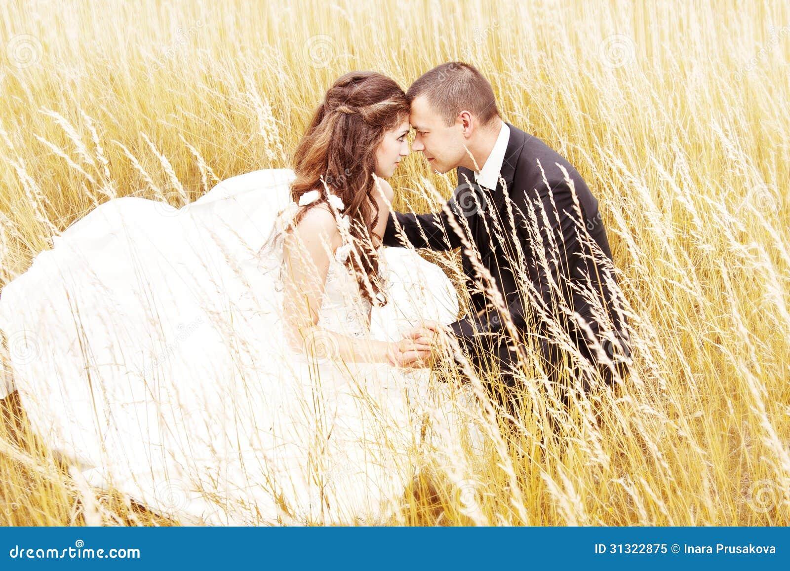 Ślubna para w trawie. Państwo młodzi outdoors