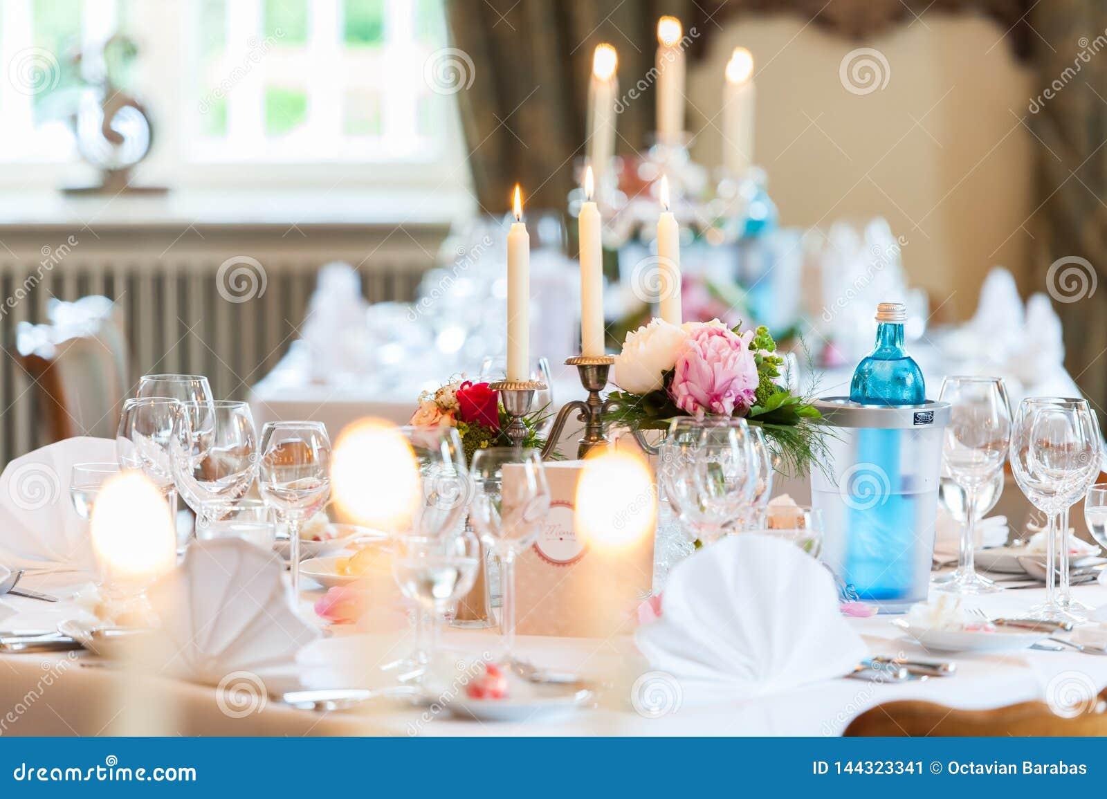 Ślubna stołowa dekoracja z świeczkami i kwiatami