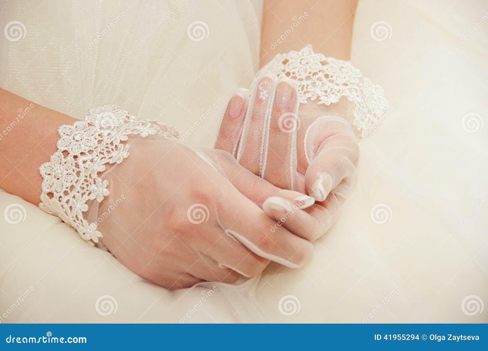 Ślubne rękawiczki na rękach panna młoda