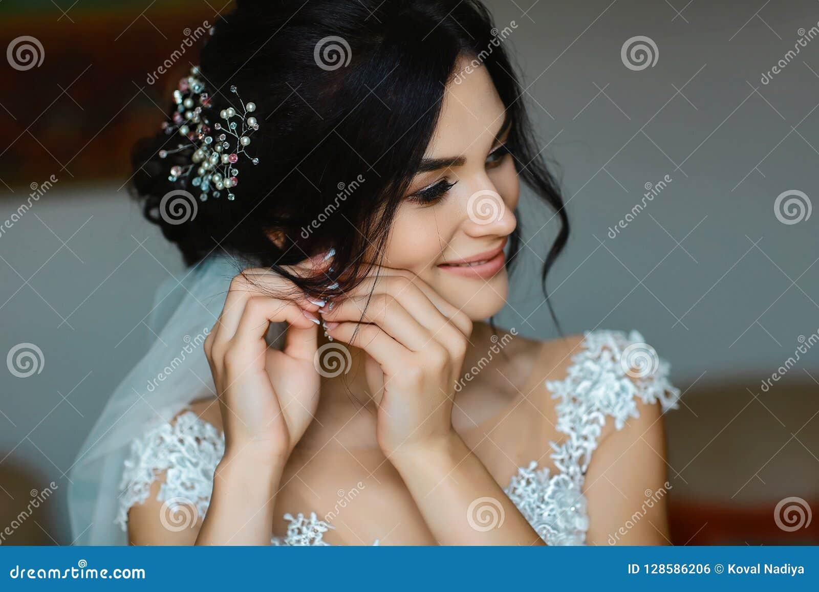 Ślubni kolczyki na żeńskiej ręce są ubranym, ona biorą kolczyki pann młodych opłaty, ranek panna młoda, kobieta w biel sukni