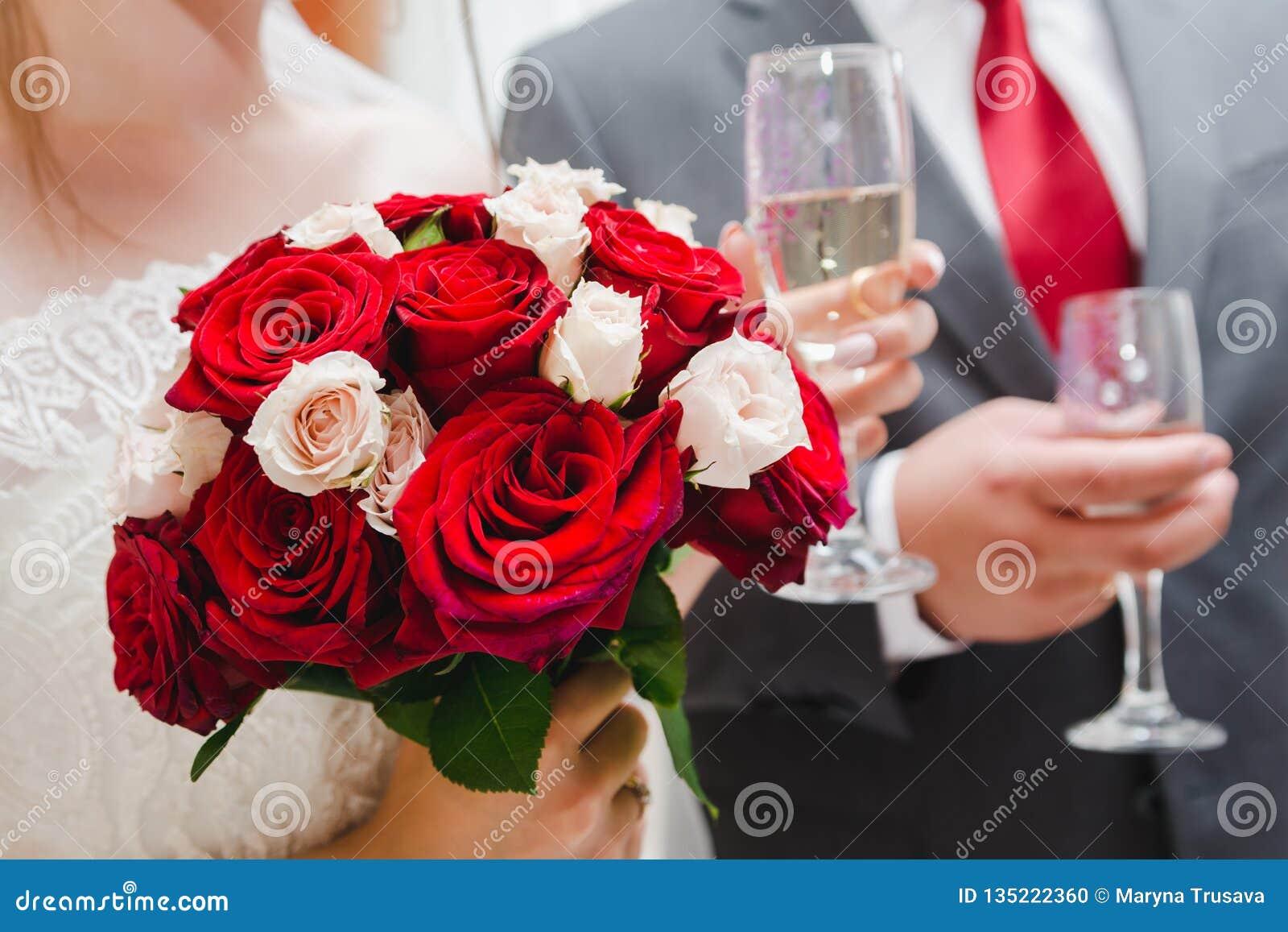 Ślubny bukiet czerwone, białe róże w ręce i ręka