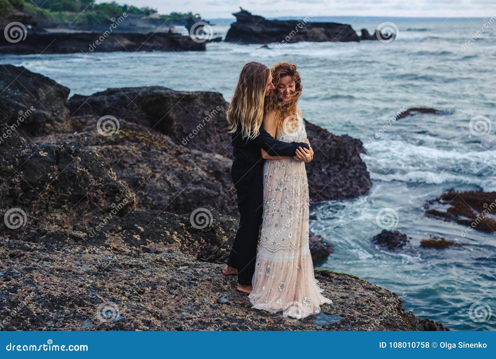 Ślubny lovestory para małżeńska blisko oceanu przy zmierzchem, właśnie