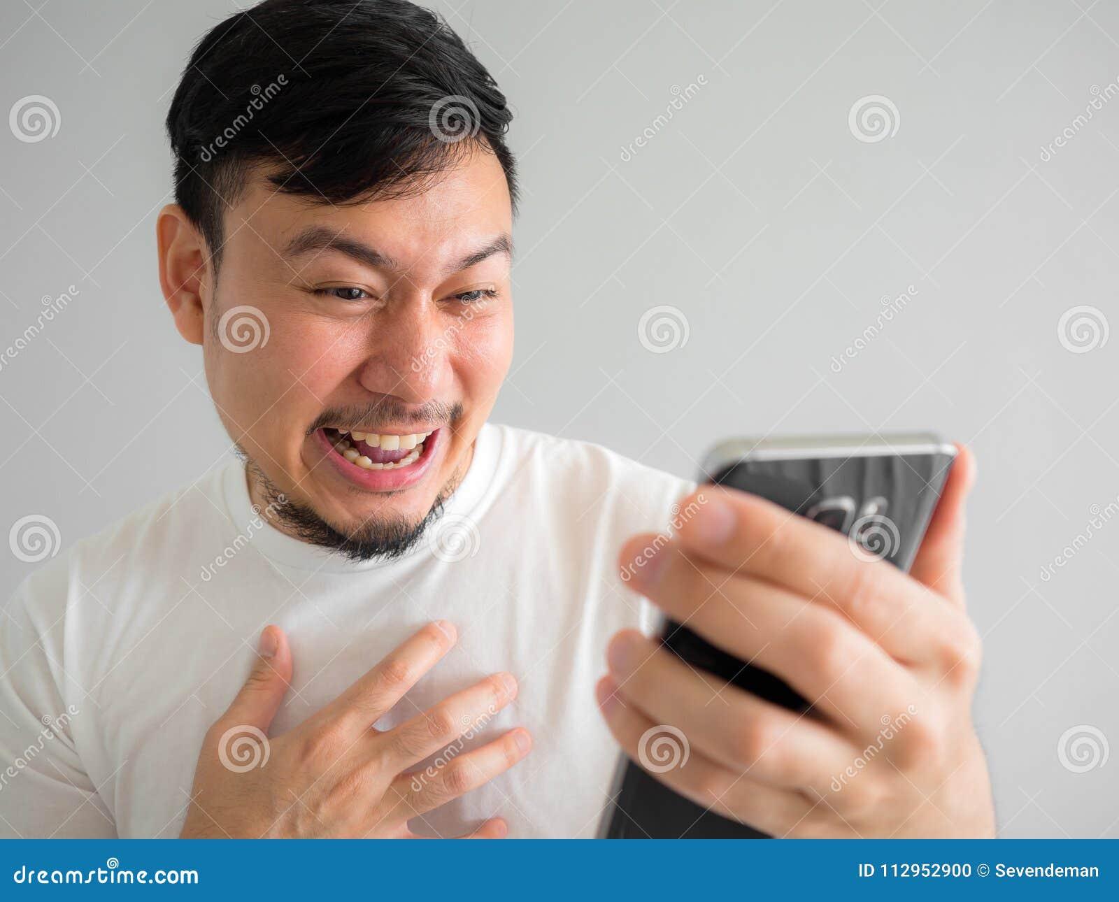 Śmieszna śmiech twarz ogląda śmieszną teledysk część w socjalny w smartphone mężczyzna