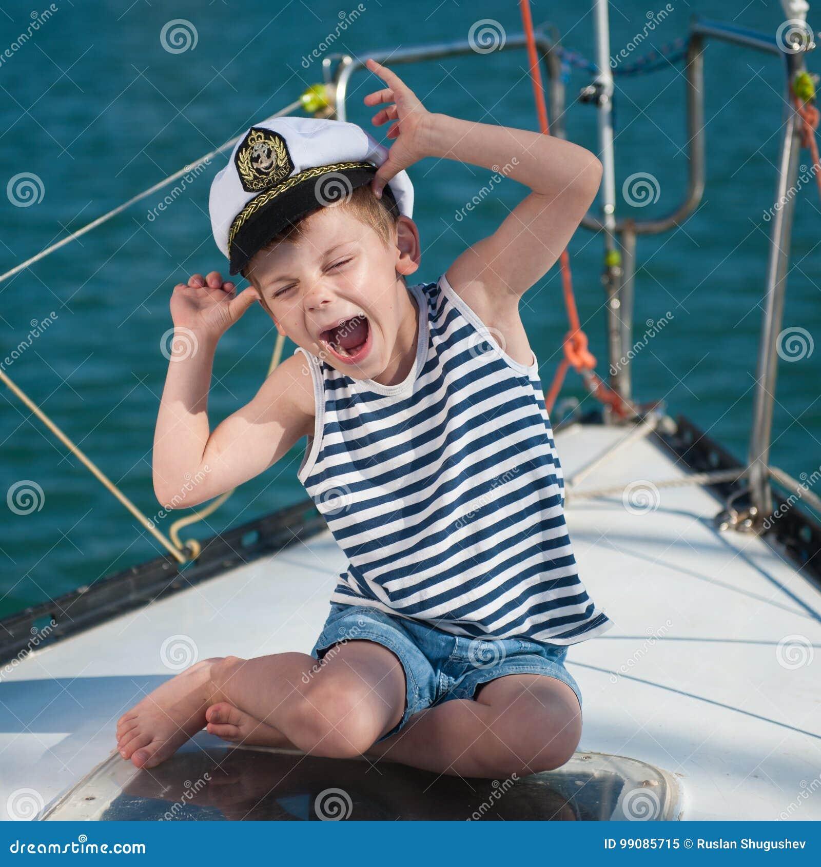 Śmieszna chłopiec jest ubranym kapitanu kapeluszowego obsiadanie na pokładzie luksusowa łódź