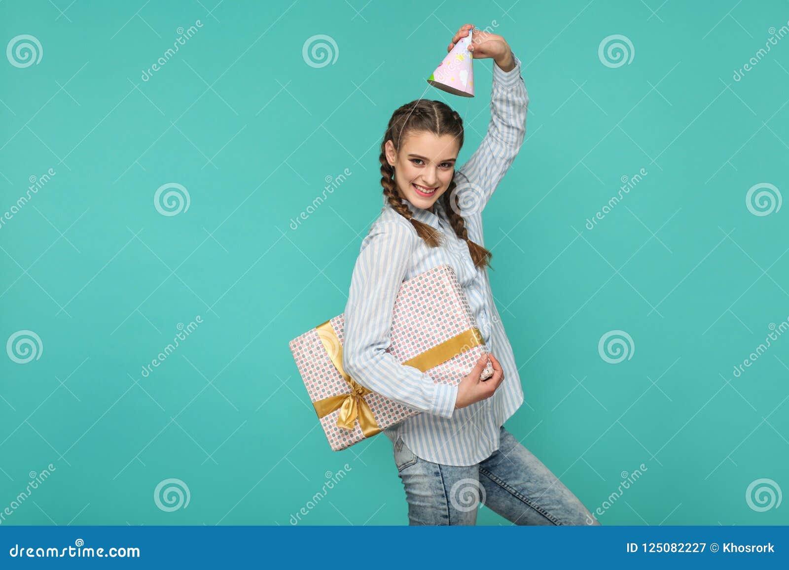 Śmieszna dziewczyna w pasiastej błękitnej koszulowej pozyci z kropkowanym prezenta pudełkiem a